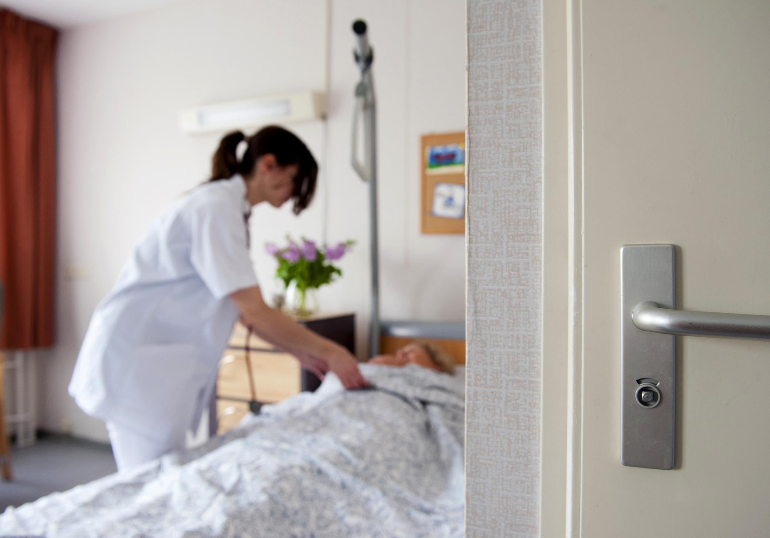 Een dokter neemt een kijkje bij een bedlegerige vrouw in een aanleunwoning. Foto: ANP / Roos Koole