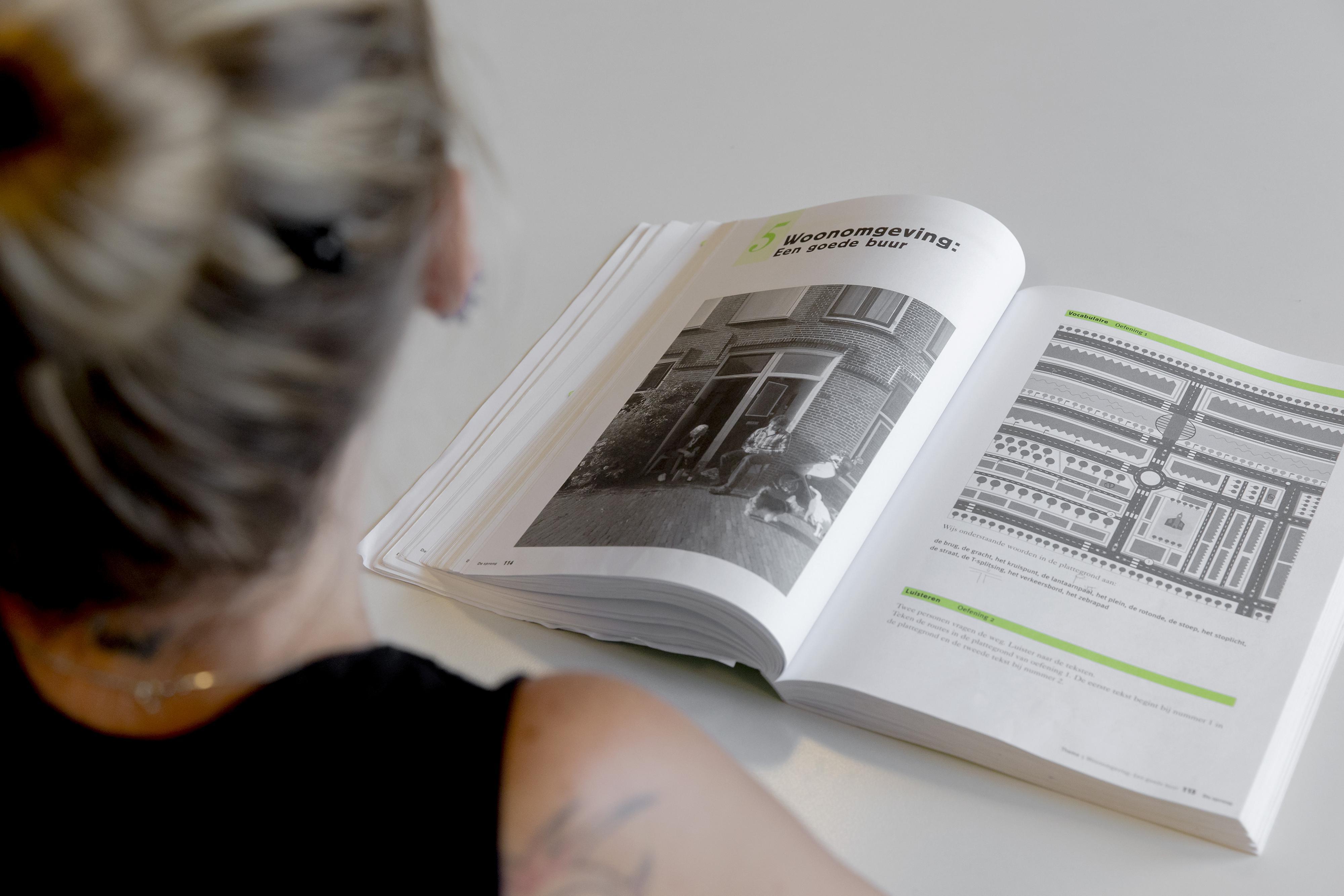 Een cursist van het Haagse ROC Mondriaan leest een lesboek tijdens een les Nederlands voor anderstaligen. Foto: ANP