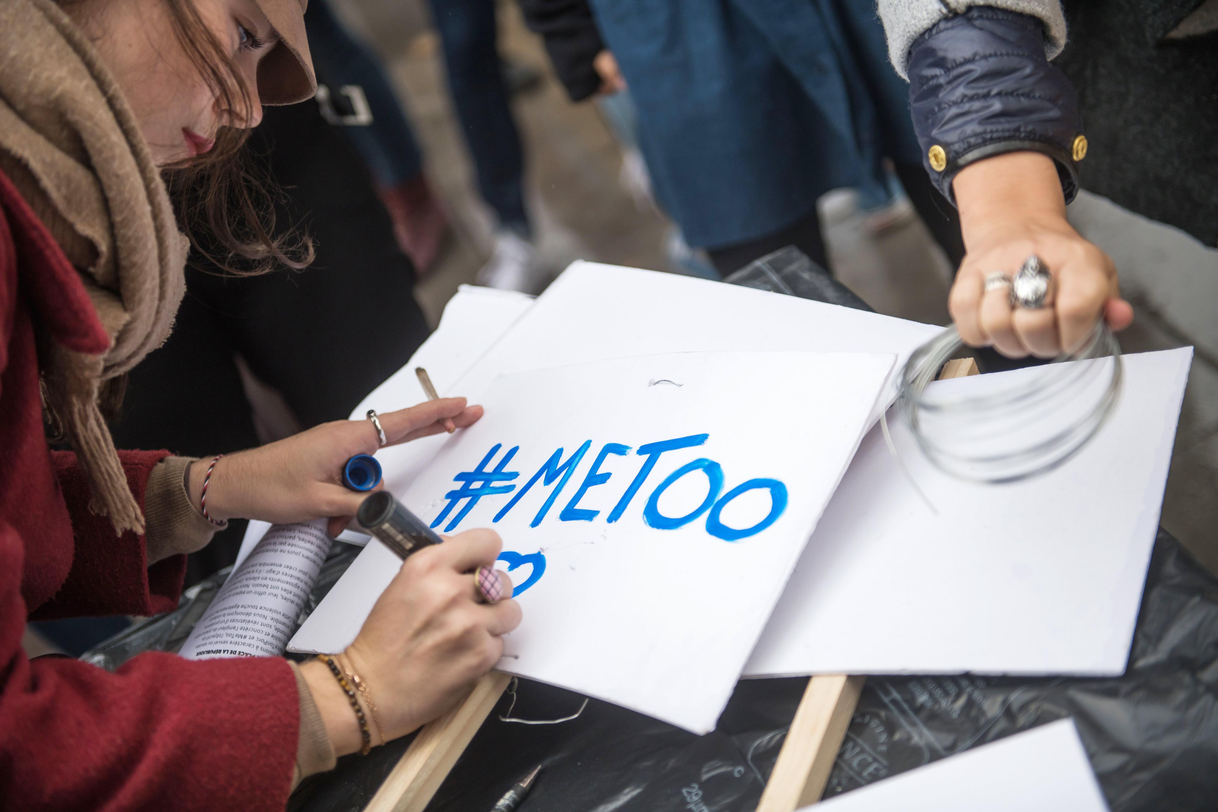 Een vrouw schrijft de #MeToo-slogan op een bord tijdens een protestactie in Parijs, Frankrijk. Foto: EPA   Christophe Petit Tesson