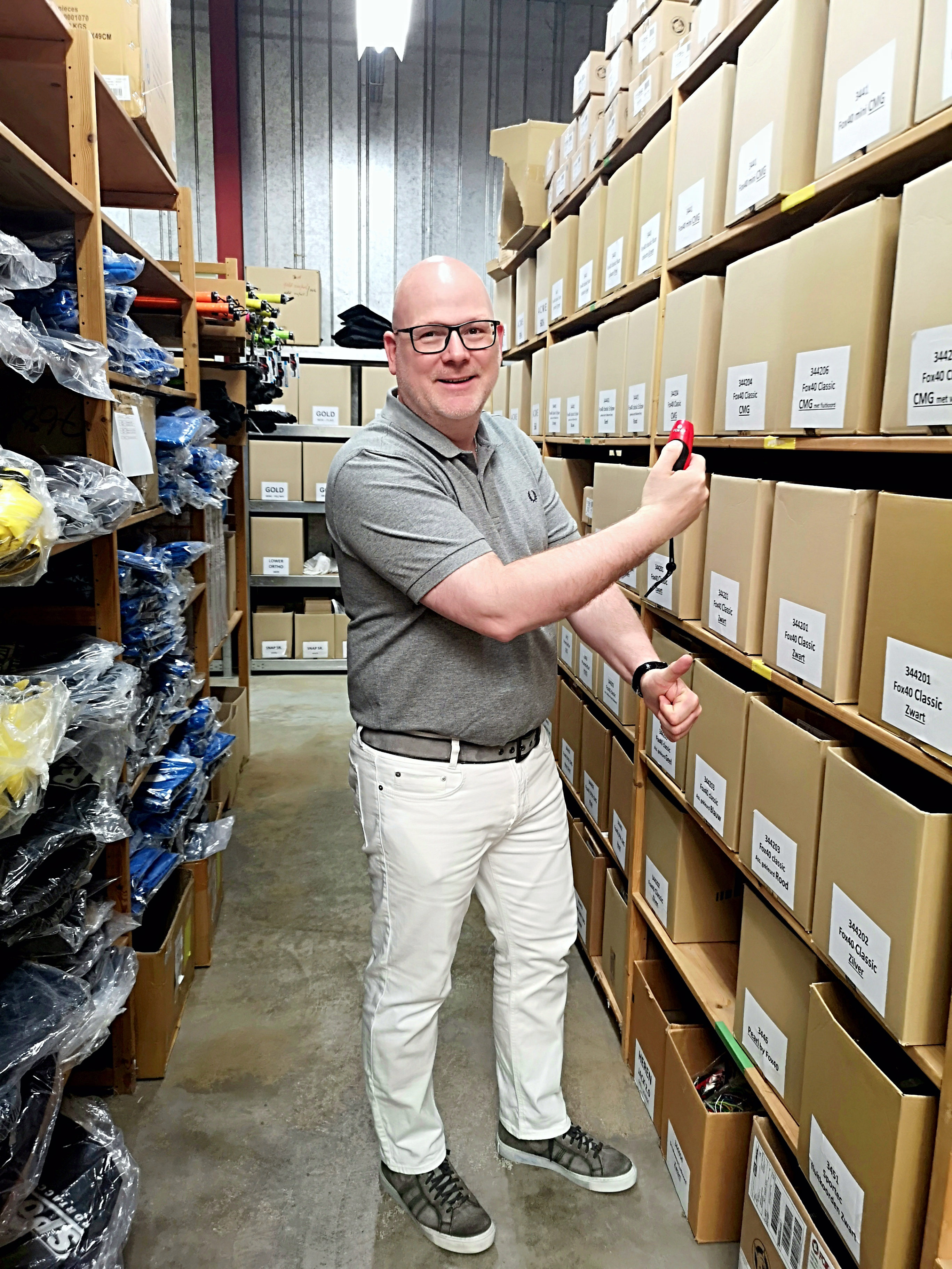 Foto van een man in een magazijn met een e-fluit in z'n hand