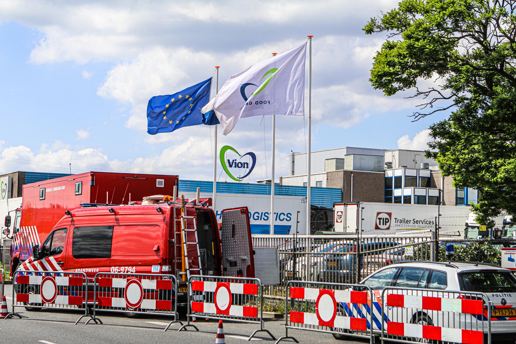 Een foto van Vleesbedrijf Vion afgesloten met hekken en rode borden, een politieauto en brandweerauto staan in beeld.