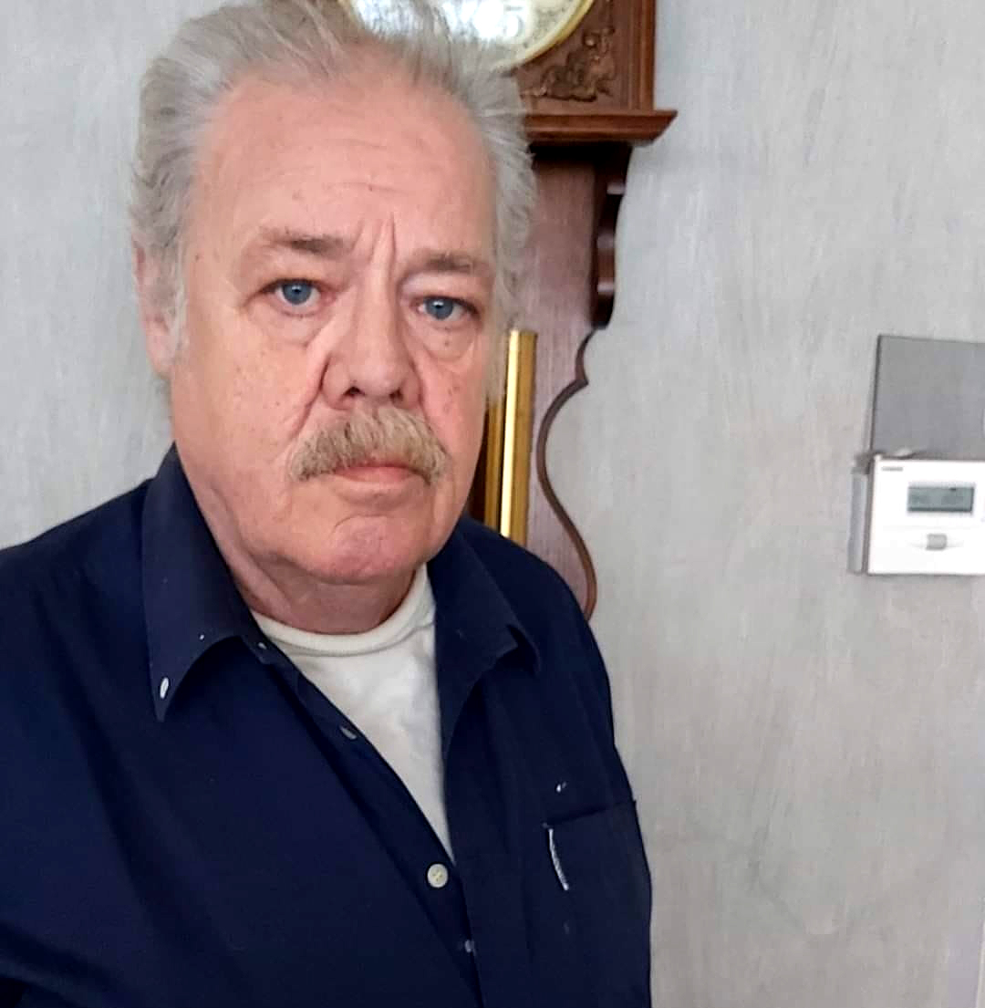 Een foto van een serieus kijkende oudere man met snor; Jean.