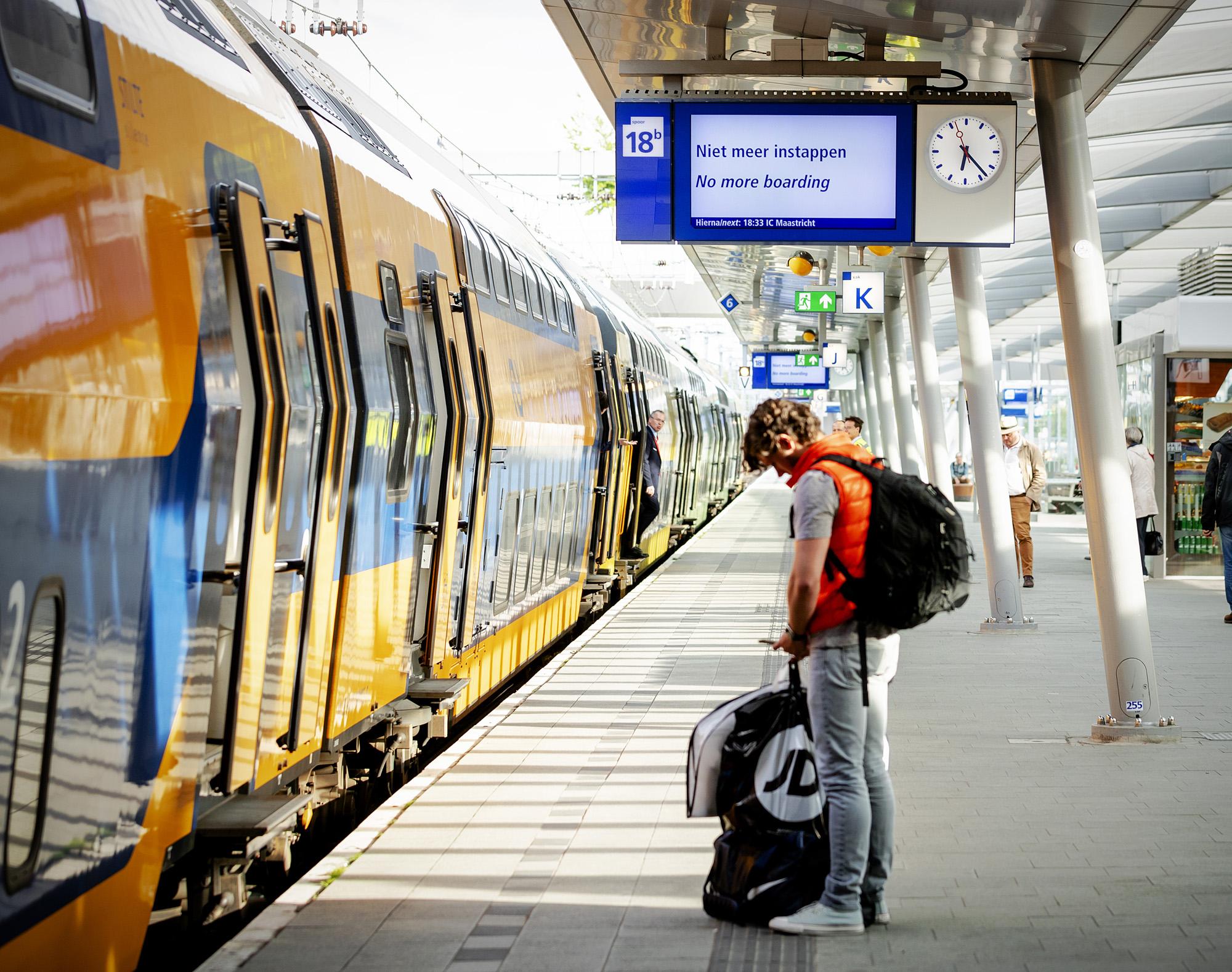 Een foto van een trein die bij een perron stilstaat. Een man in oranje bodywarmer staat op het perron op zijn telefoon te kijken.
