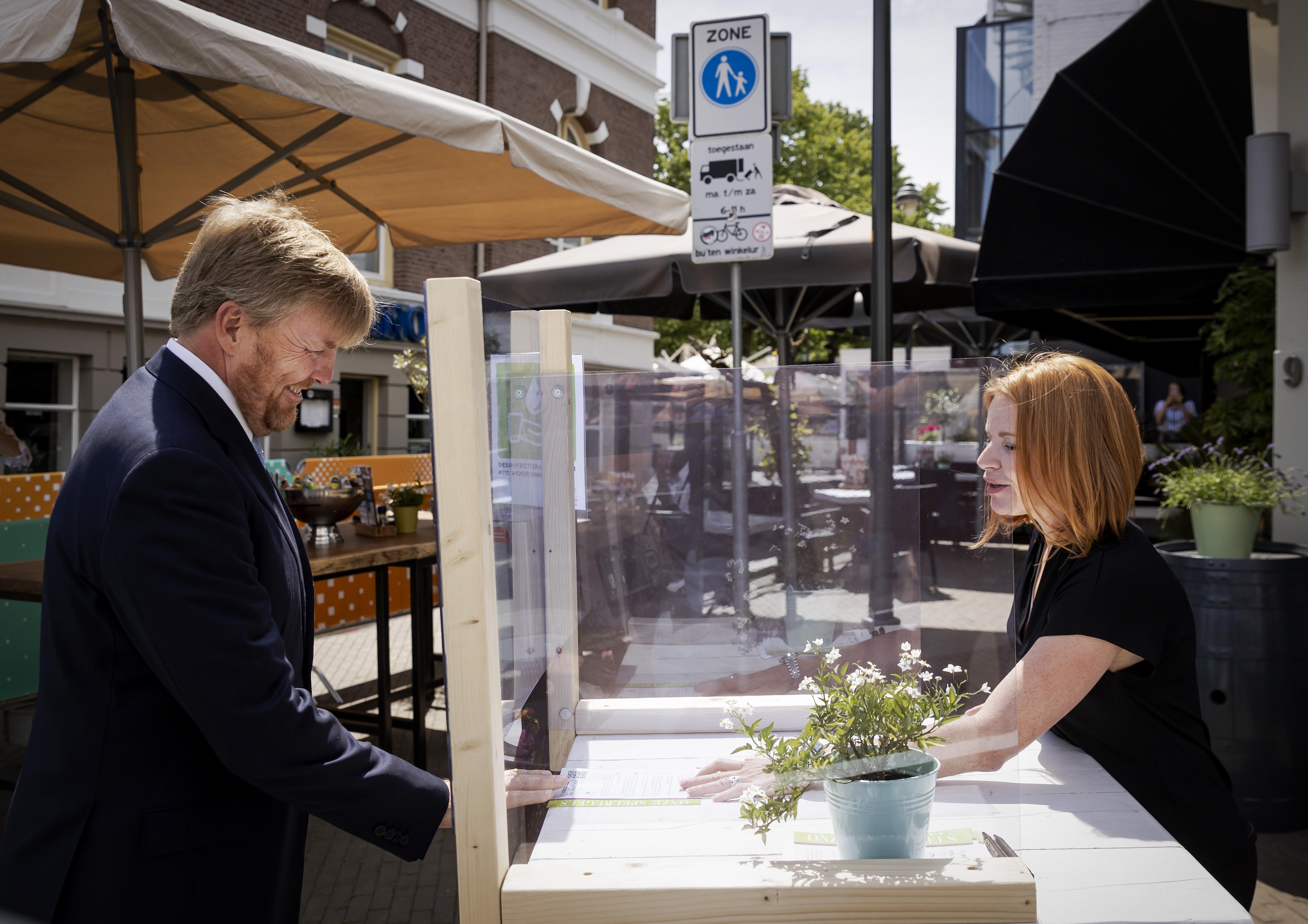 Een foto van koning Willem-Alexander die een kijkje neemt bij horeca in Apeldoorn