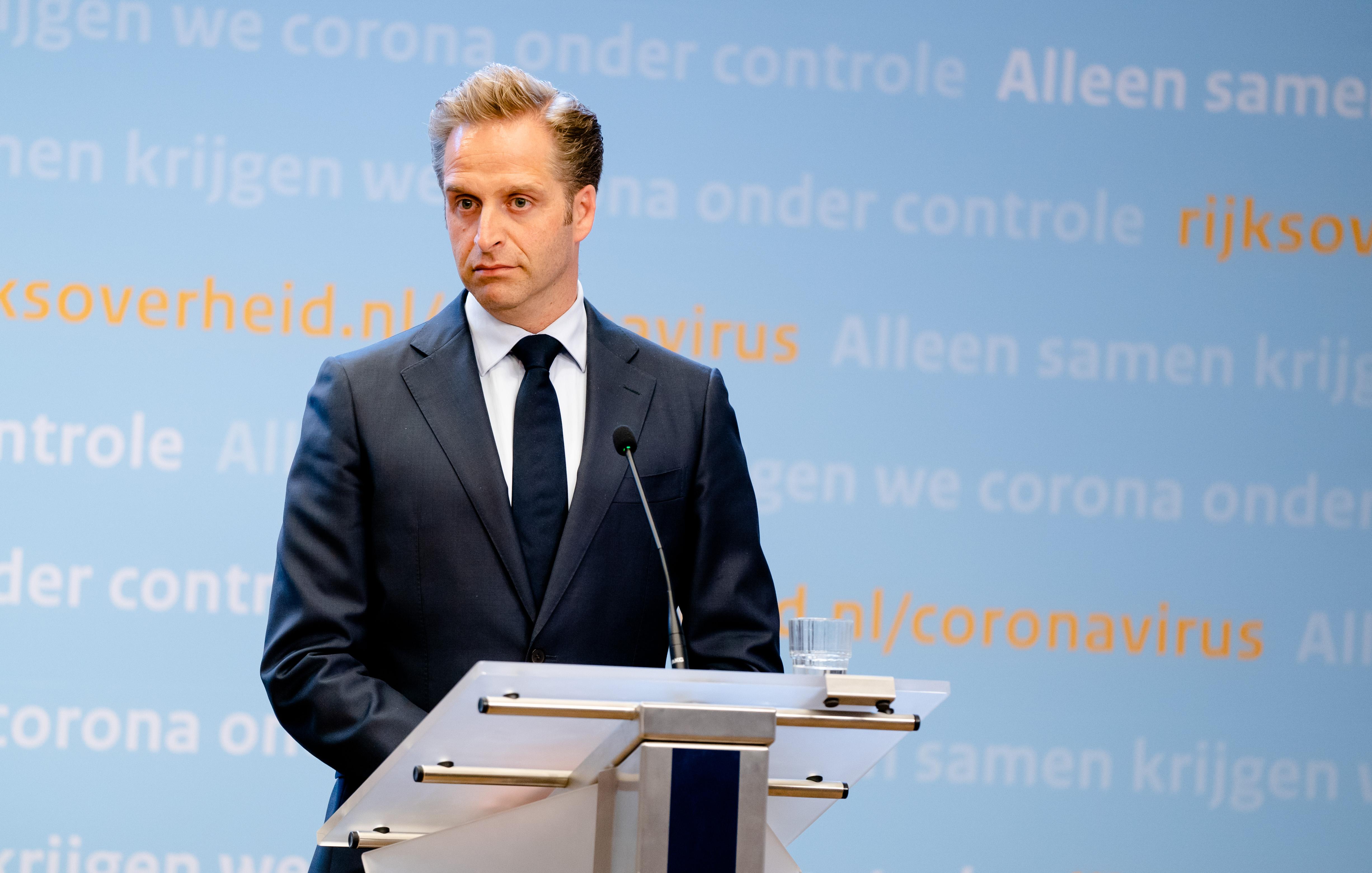 Een foto van minister Hugo de Jonge tijdens een persconferentie