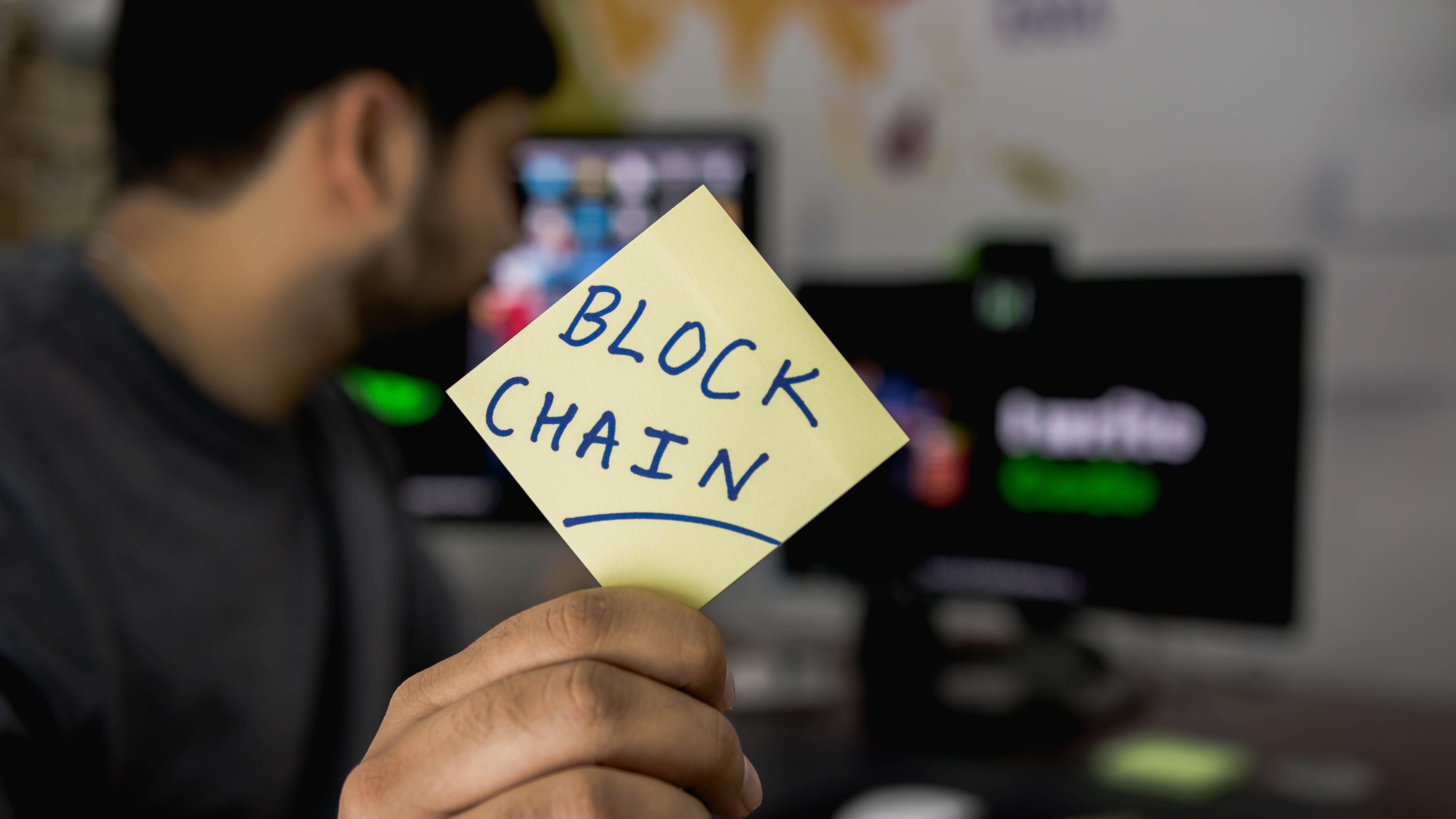 Een foto van een man met een sticker met de tekst block chain