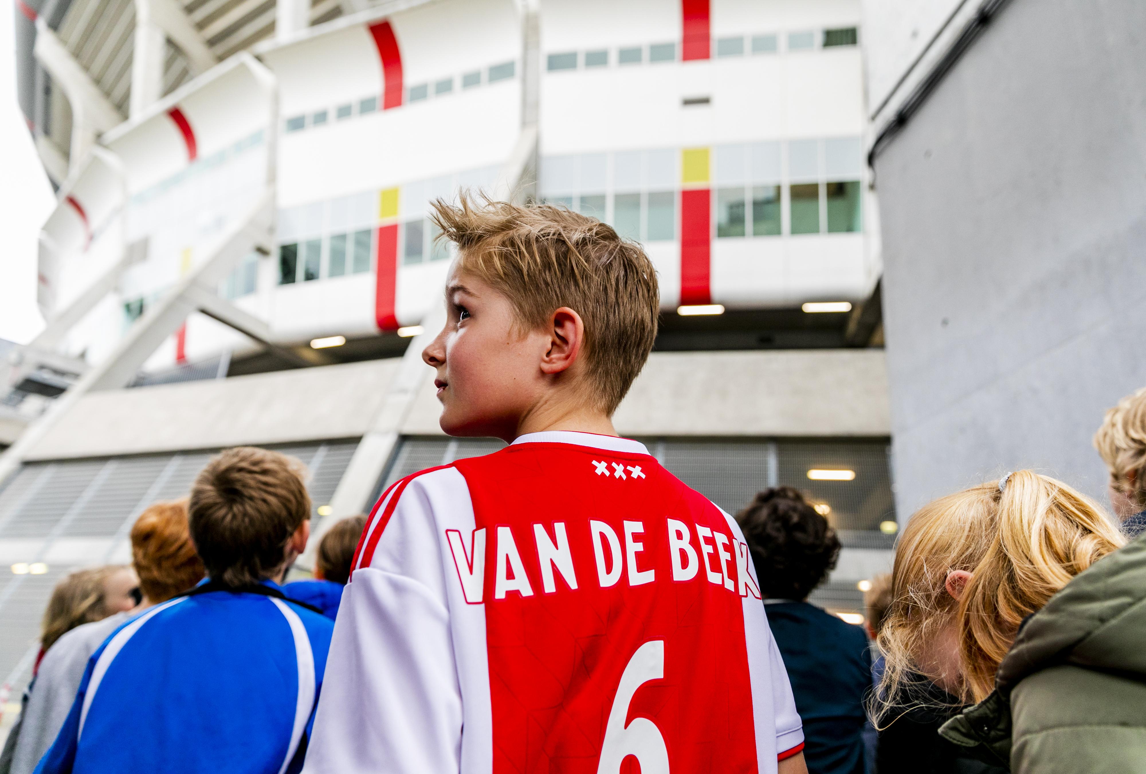 Een foto van een jonge Ajaxsupporter op weg naar de Johan Cruijff ArenA
