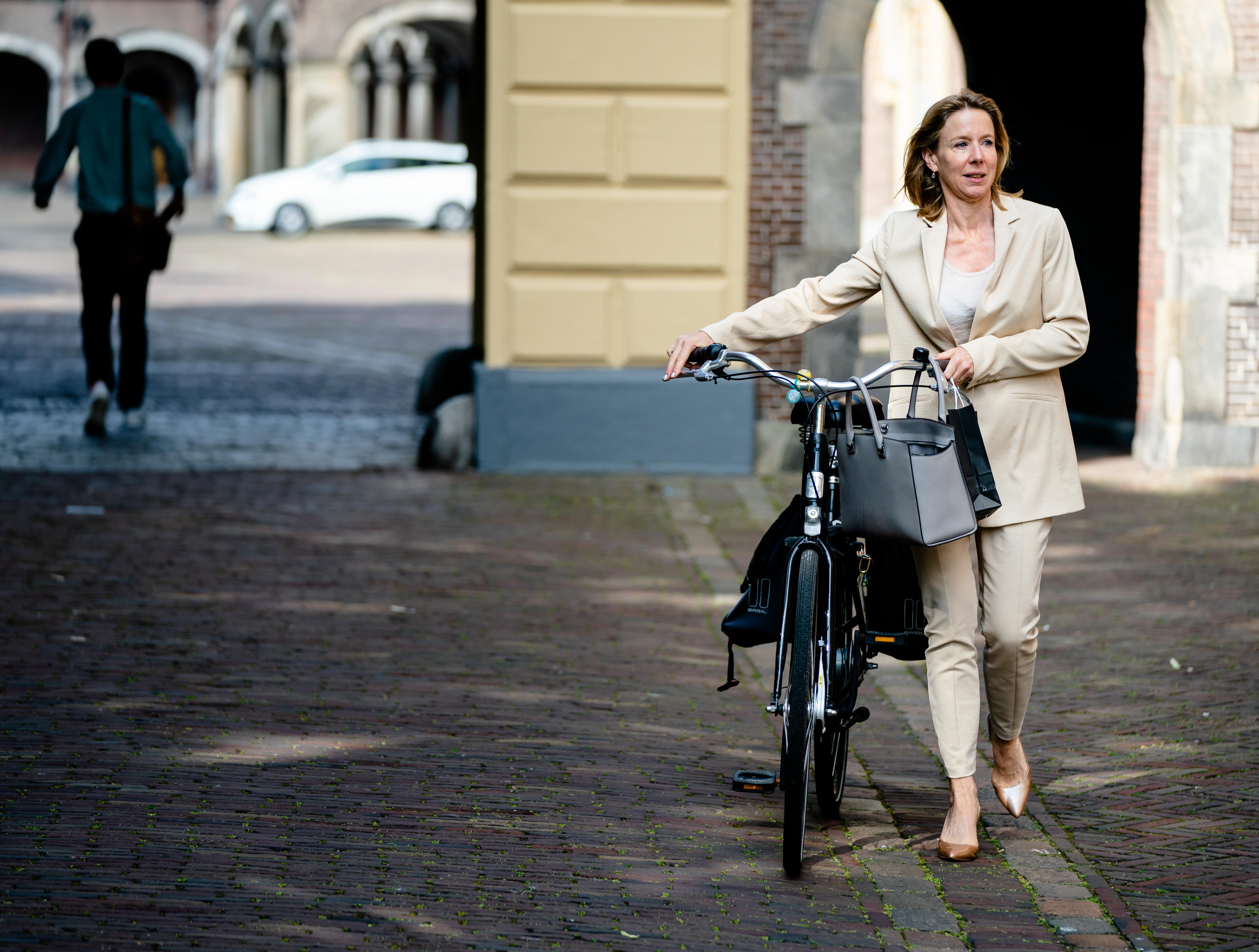 Een foto van staatssecretaris Stientje van Veldhoven, lopend naast haar fiets op het Binnenhof