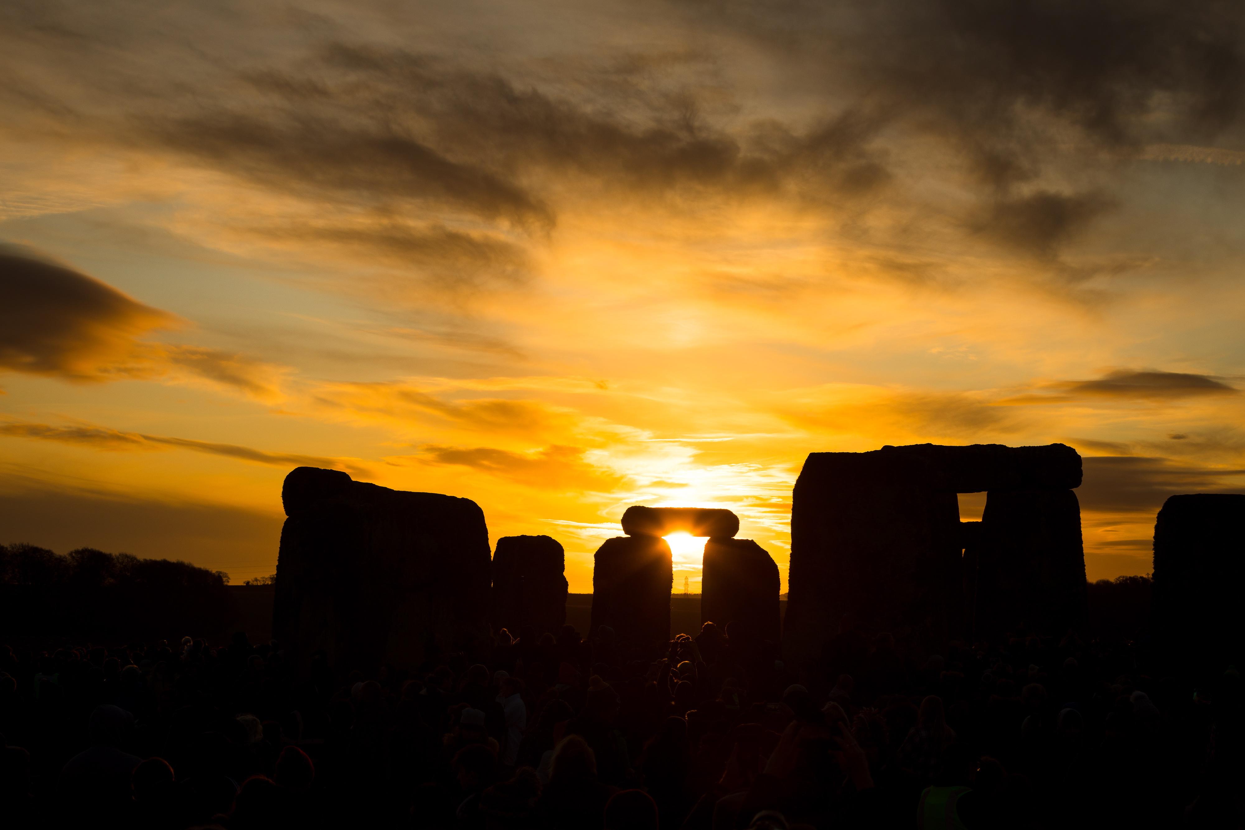 Een foto van Stonehenge als de zon achter de horizon verdwijnt.