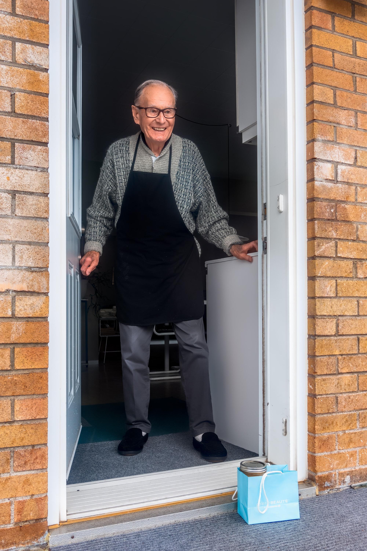 Een foto van een oudere man in de deur bij wie een tasje boodschappen op de stoep is gezet.