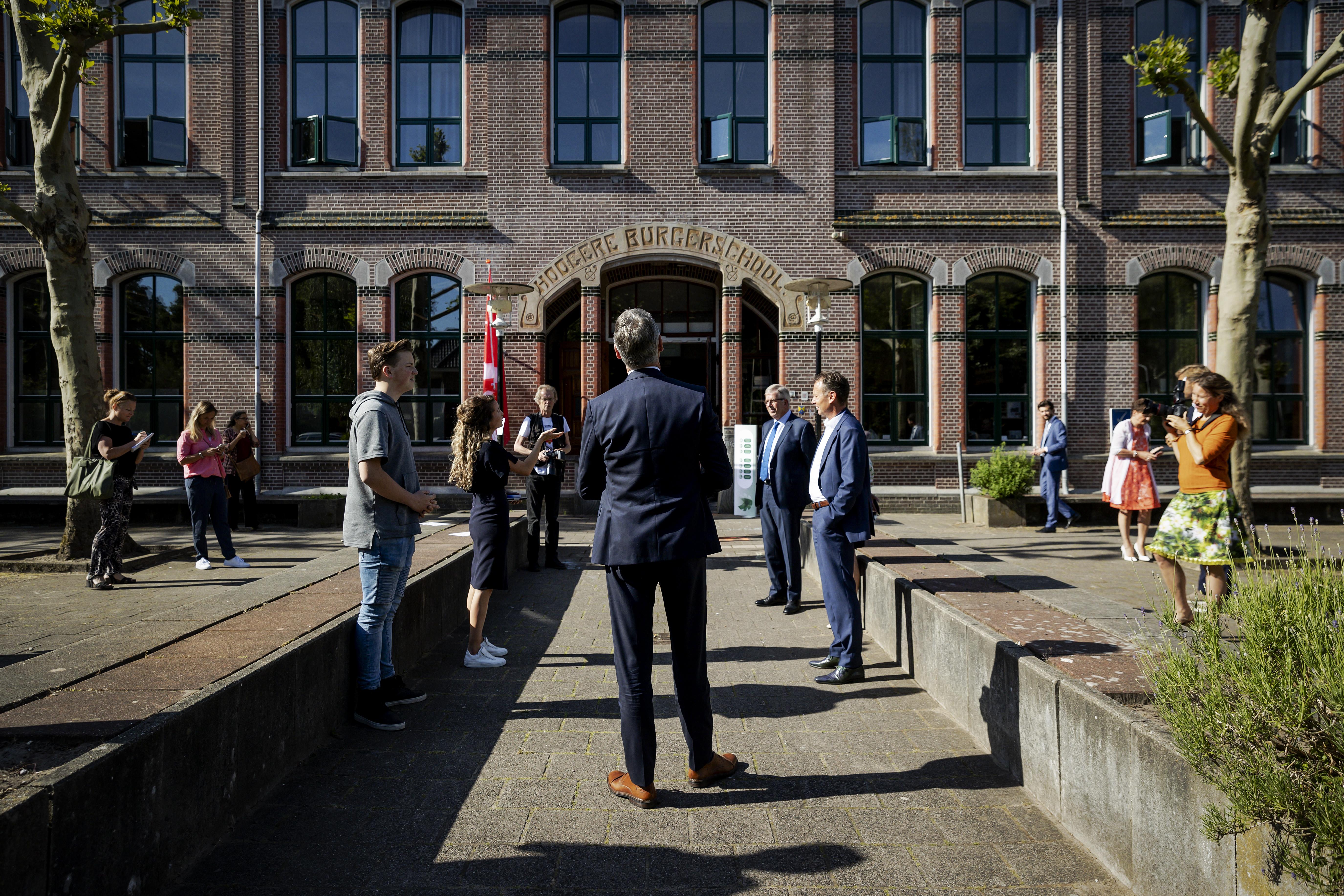 Foto van minister Slob die middelbare scholieren bezoekt