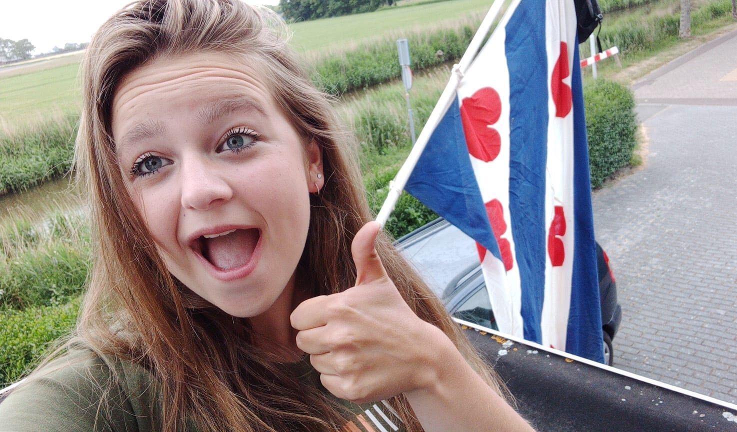 Een foto van een jonge meid die haar duim opsteekt, achter haar hangt een Friese vlag met tas eraan