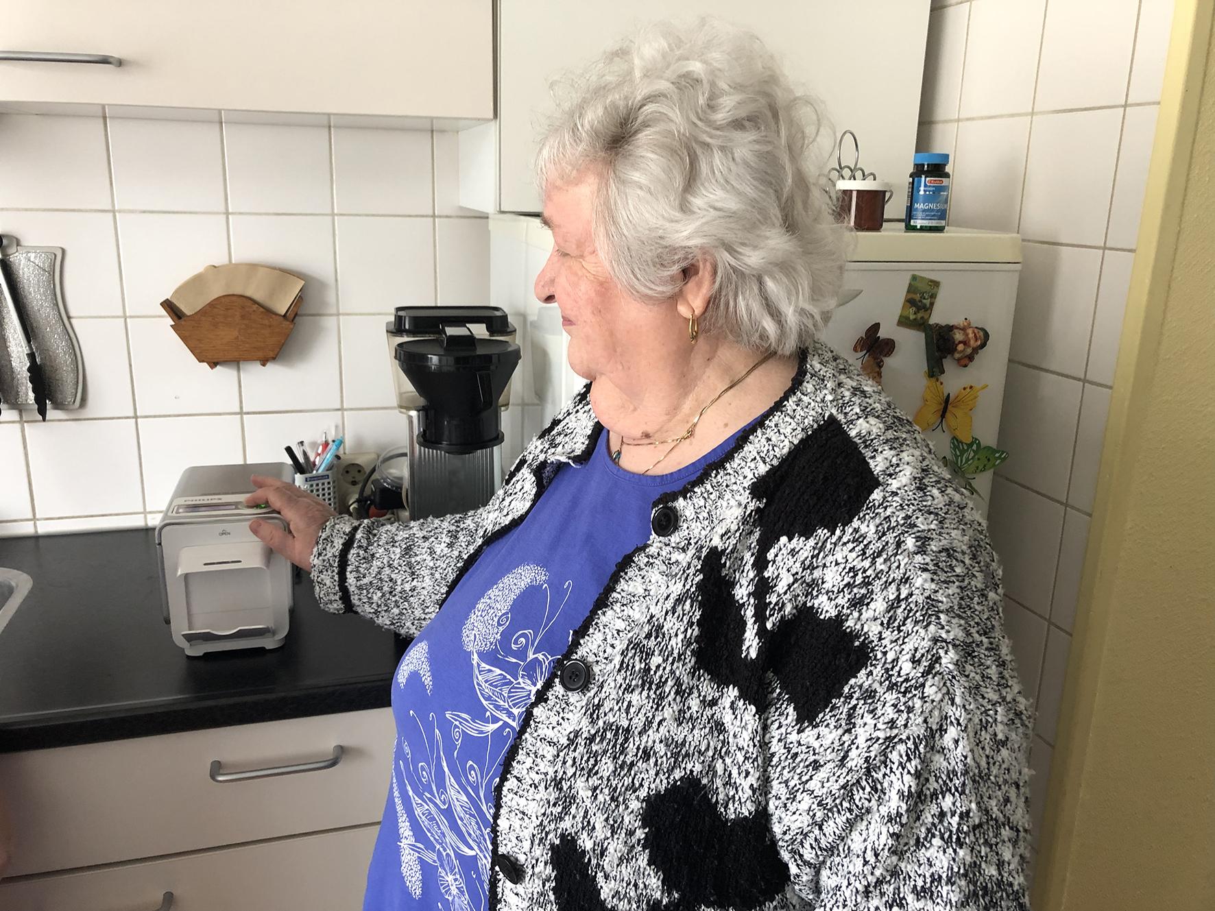 Op deze foto zie je een oudere dame bij een medisch apparaat in haar keuken thuis