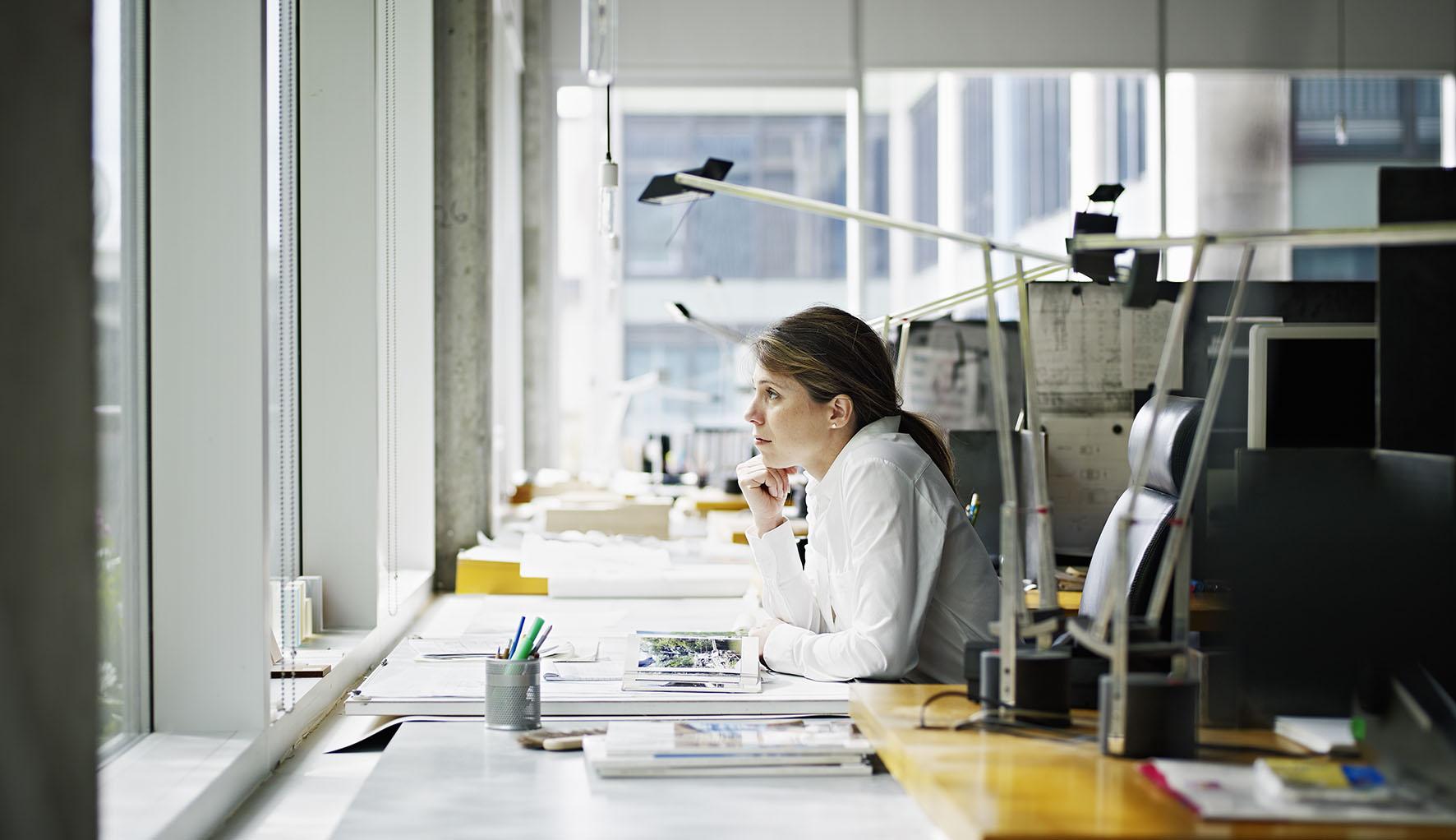 Op deze foto zit een vrouw achter haar bureau op haar werk en staart naar buiten.