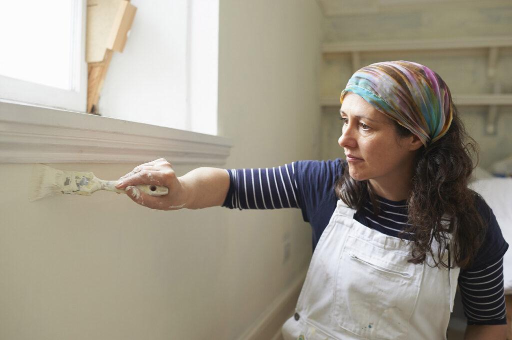 Op deze foto zie je een vrouw die aan het schilderen is.