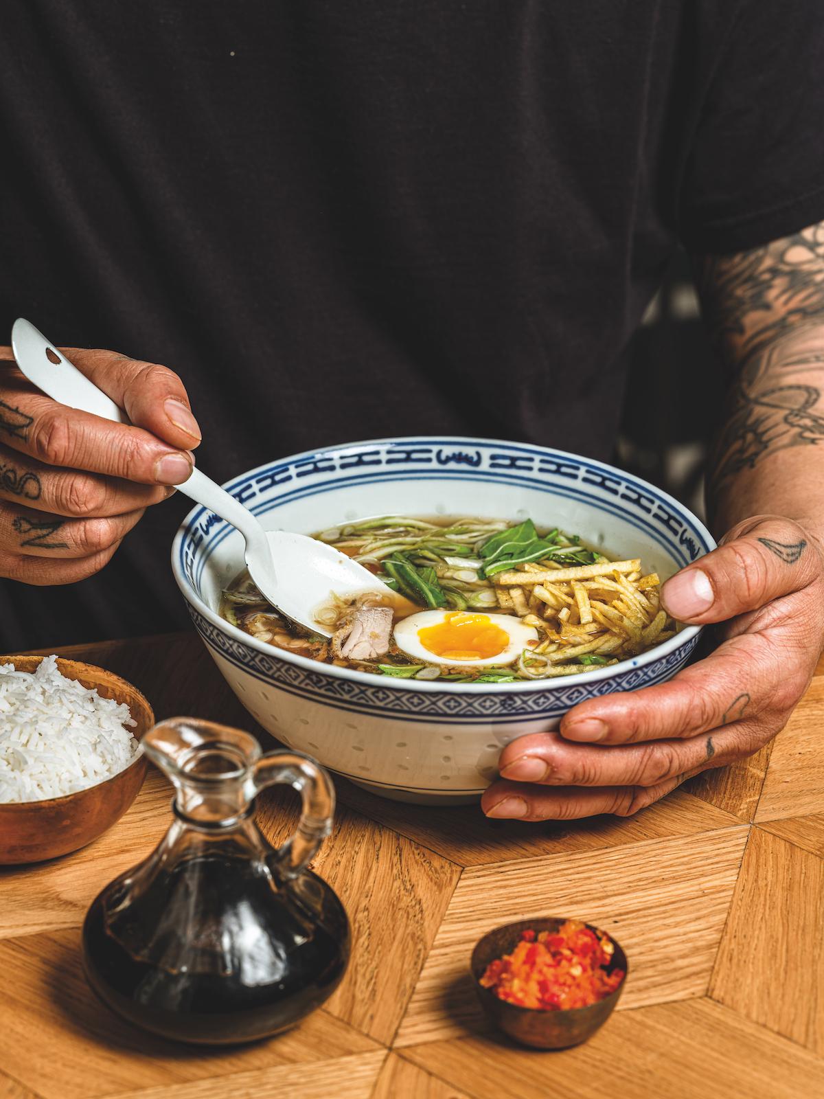 Op deze foto zie je een man met een bord van Moeders' saotosoep van chefkok London Loy