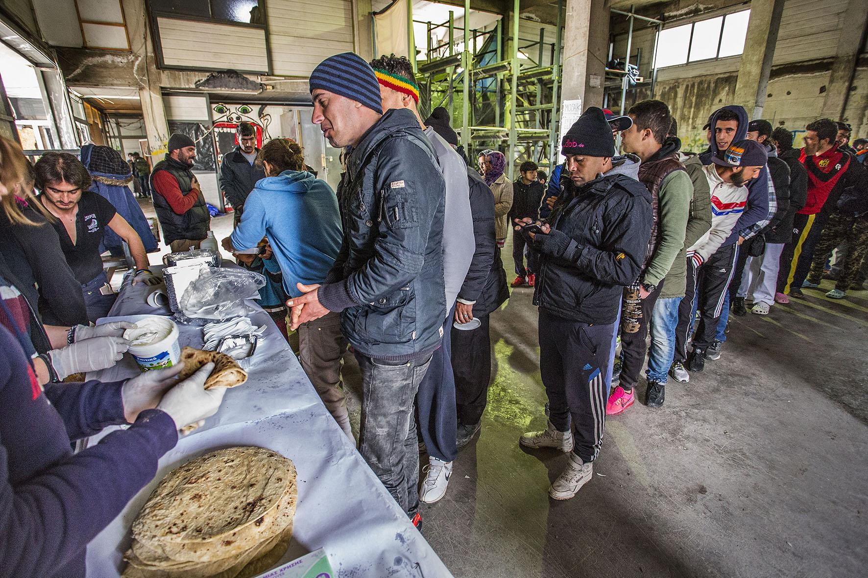 Op deze foto zie vluchtingen in de rij staan voor eten in een leegstaande cementfabriek op Lesbos.