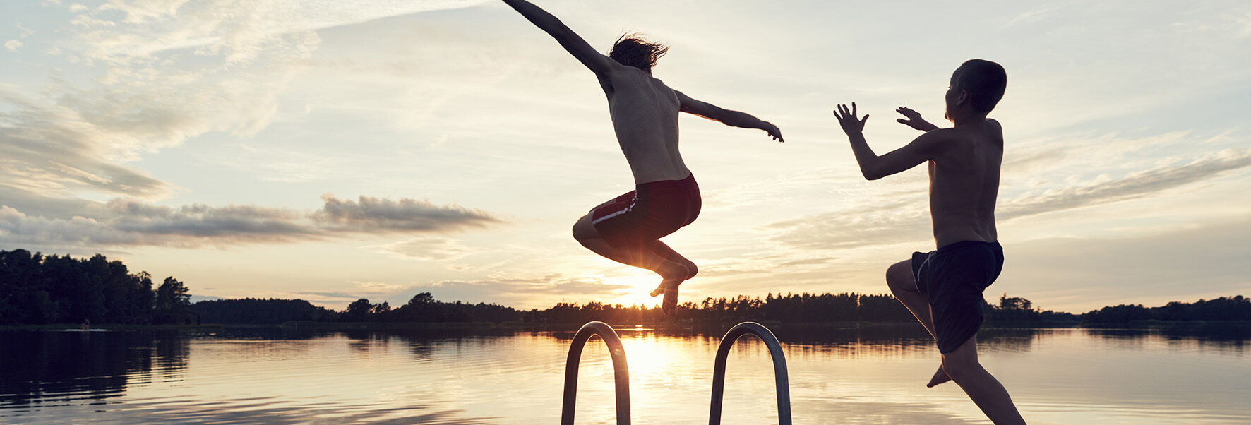 Op deze foto zie je twee jongen in het water springen tijdens de zomer. er is zomers weer op komst.
