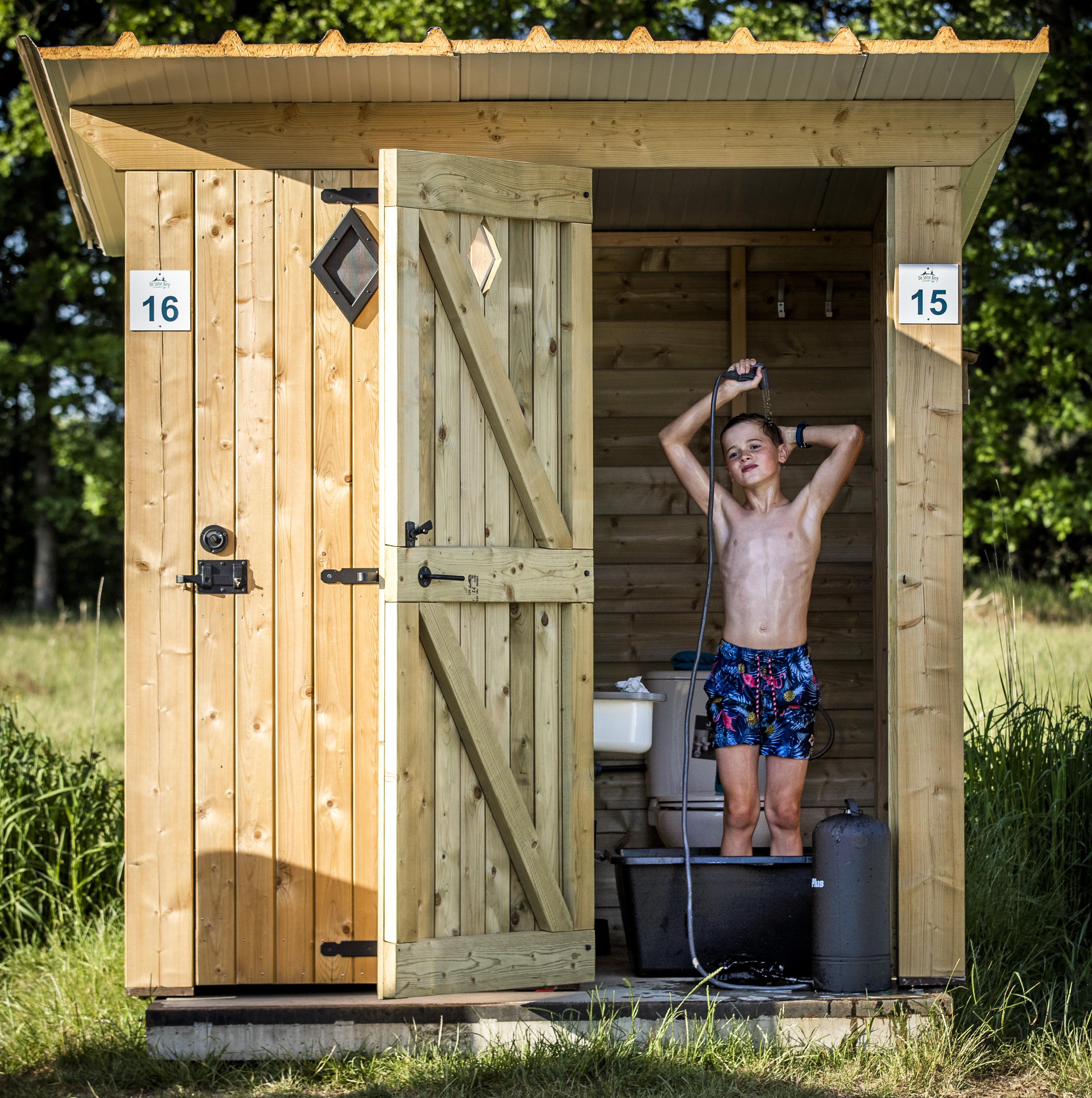 Een foto van een jonge campinggast in een privé-sanitair in Garderen.