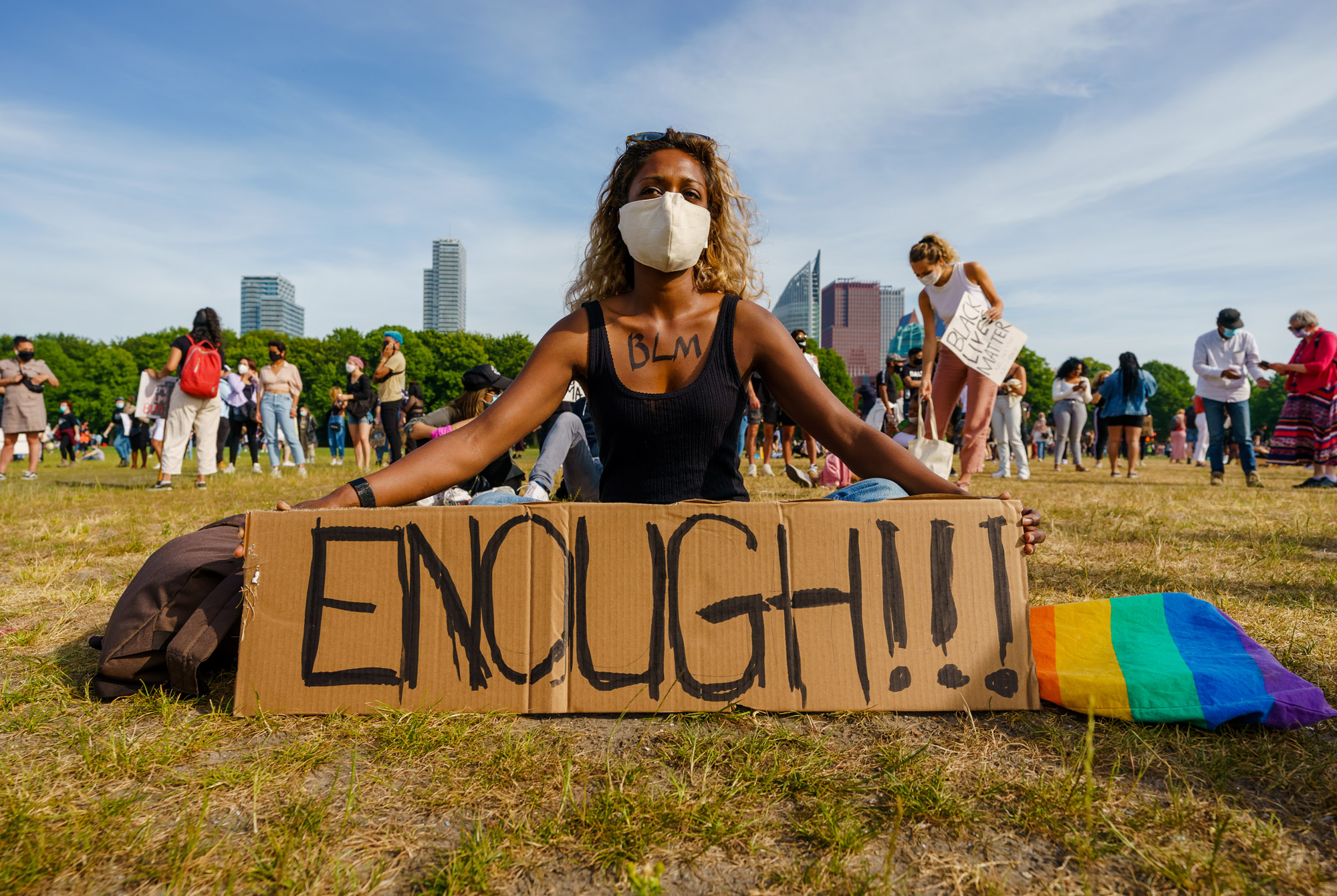 Een foto van een jonge vrouw met mondkapje op het malieveld in den haag, ze zit met een bord waarop 'enough' staat. Op de achtergrond meer demonstranten en de stad Den Haag.