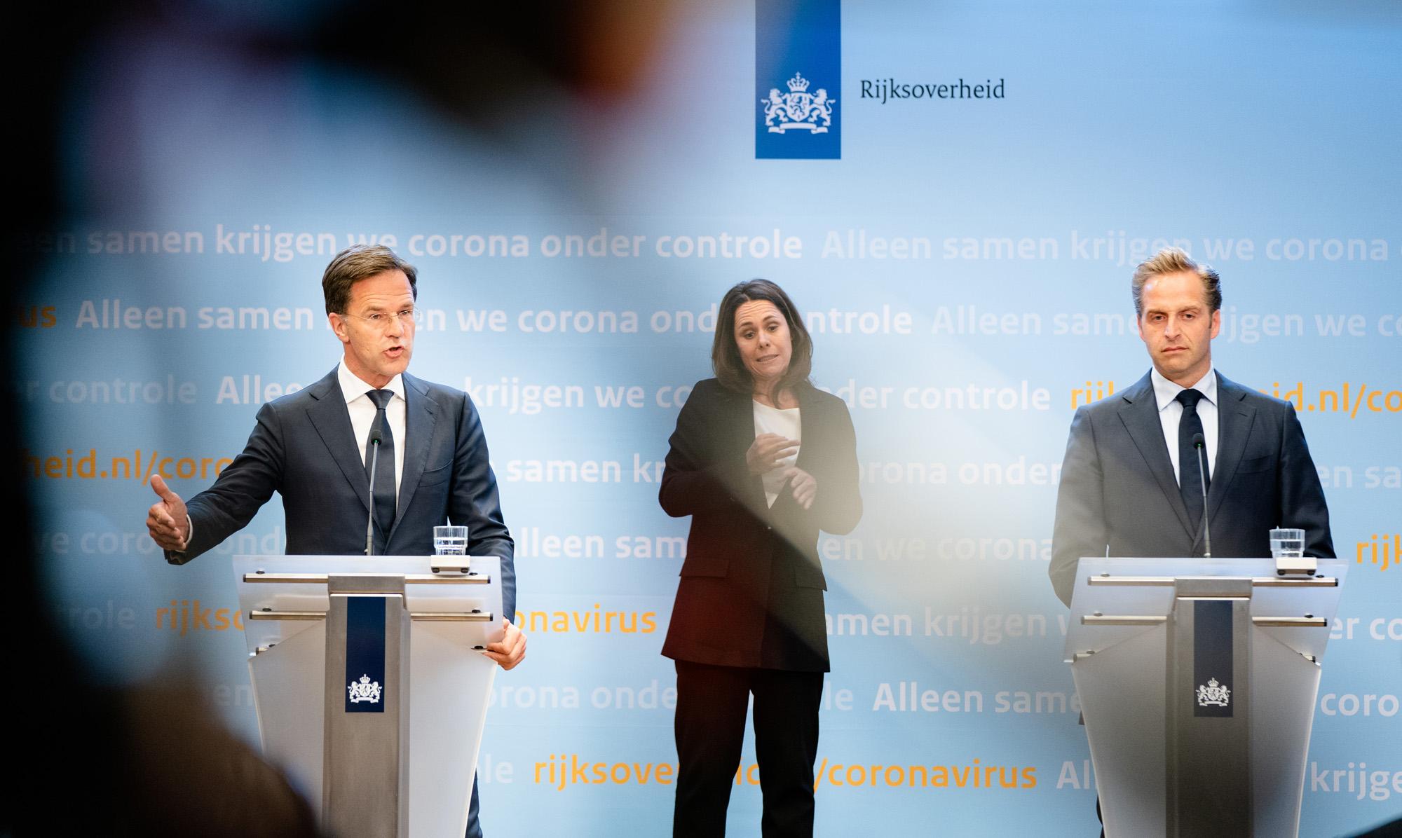 Een foto van premier Rutte, gebarentolk Irma en minister de jonge tijdens een persconferentie