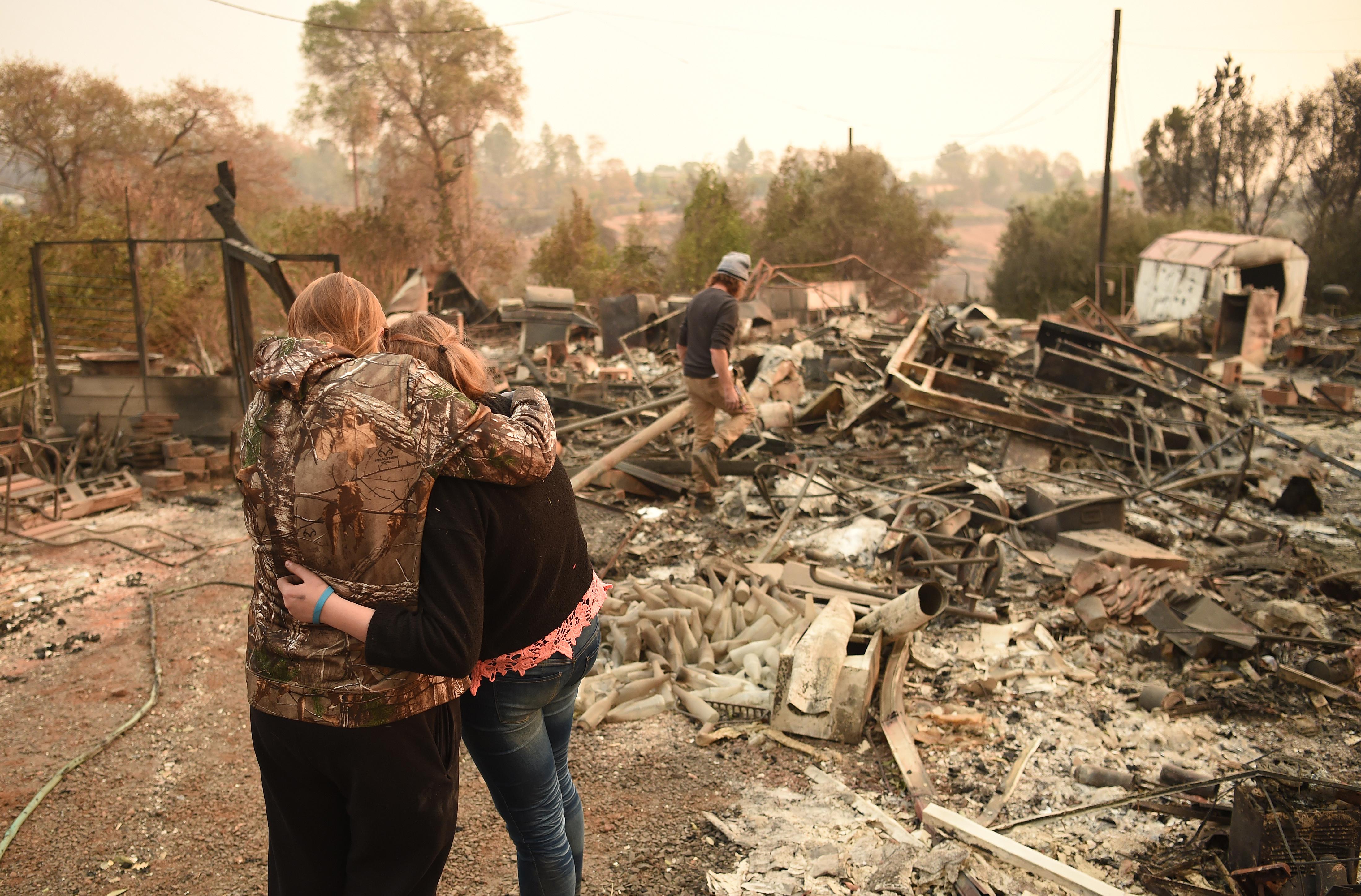 Op de foto twee mensen die elkaar troosten in de puinhopen van de bosbranden in Paradise.