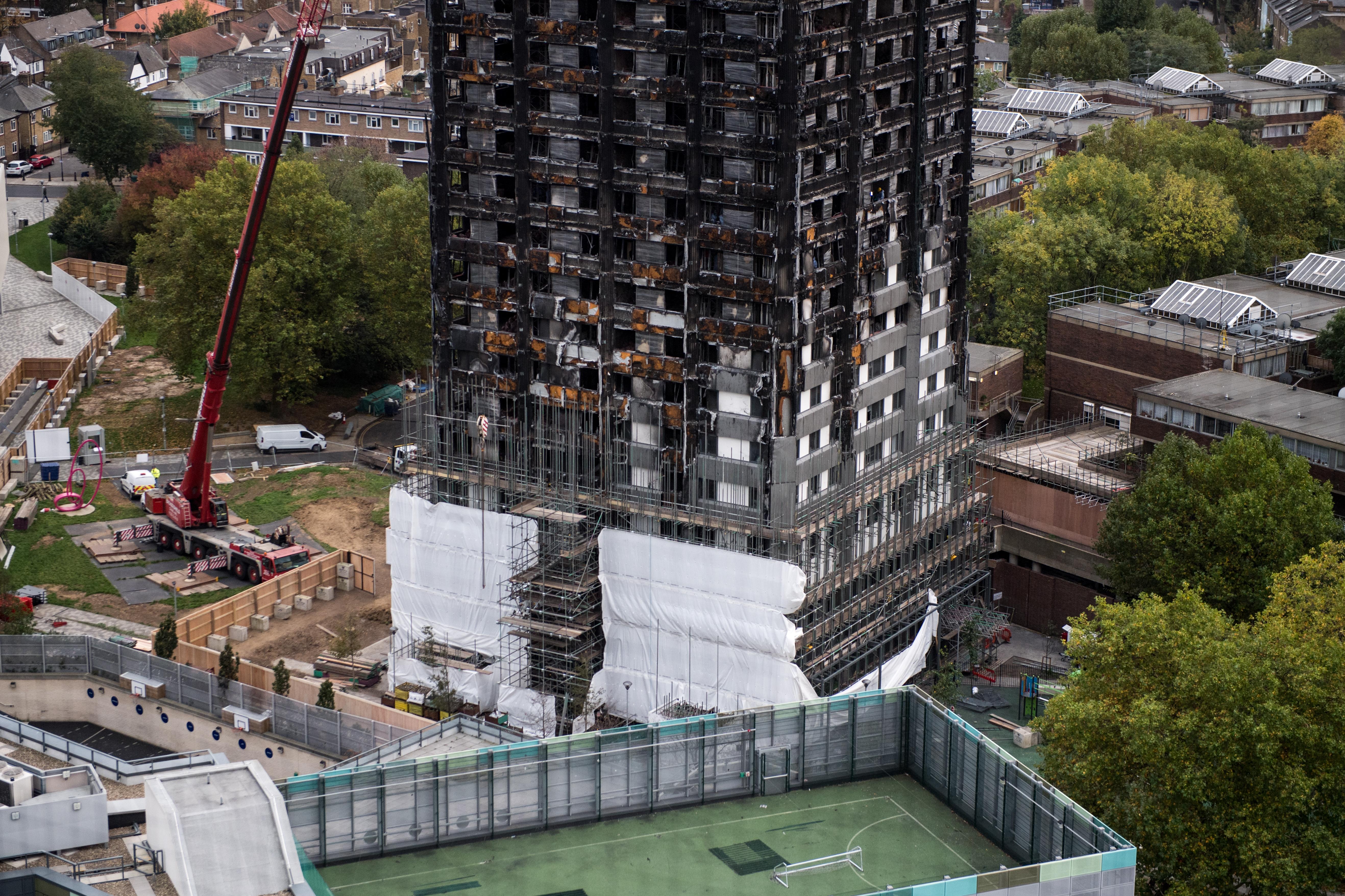 Op de foto de zwartgeblakerde woontoren Grenfell in Londen.