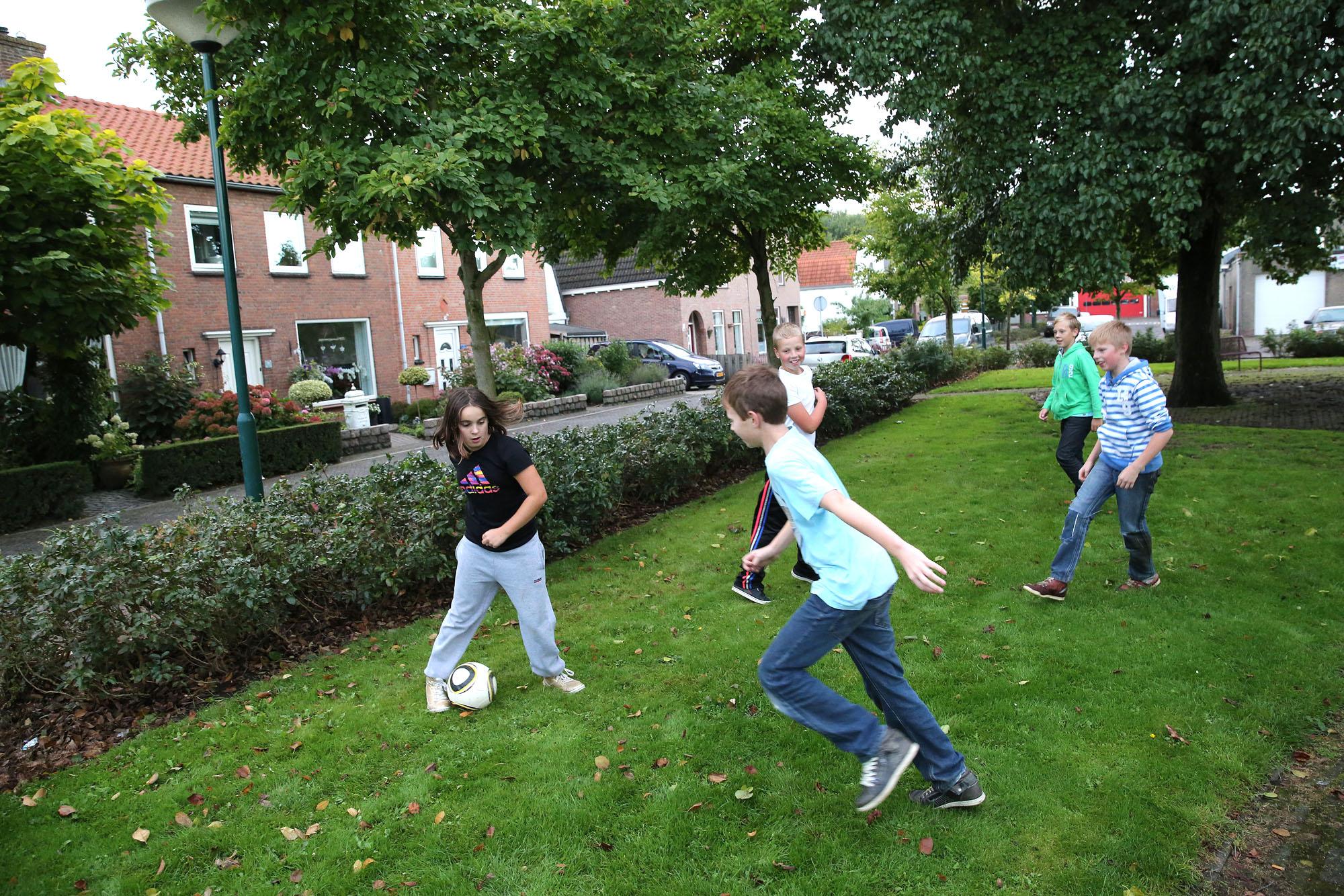 Een foto van kinderen die een potje voetballen in een plantsoen.