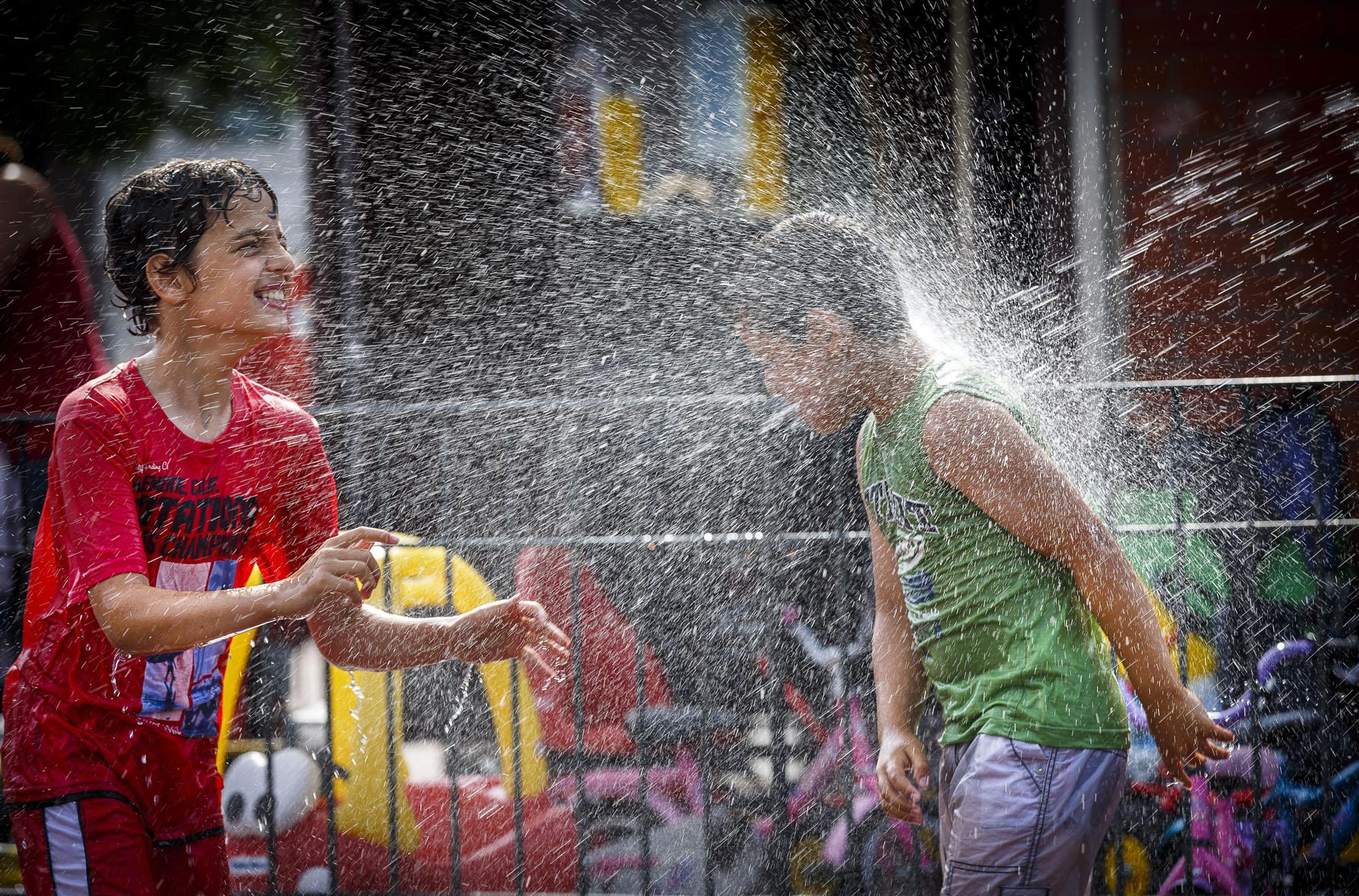 Een foto van twee jongens die buiten spelen en helemaal nat worden gespoten met water