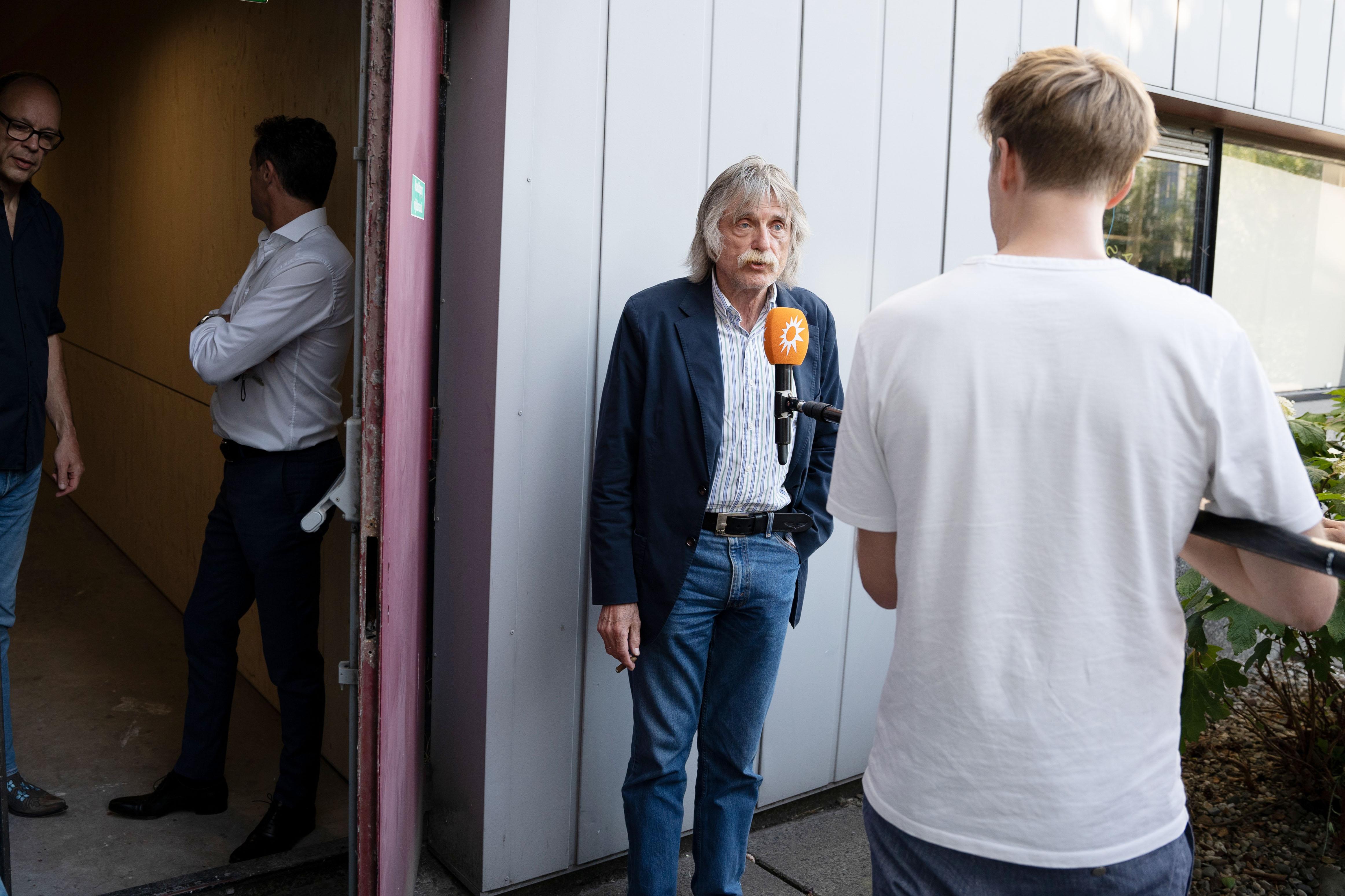 Een foto van Johan Derksen die een interview geeft.