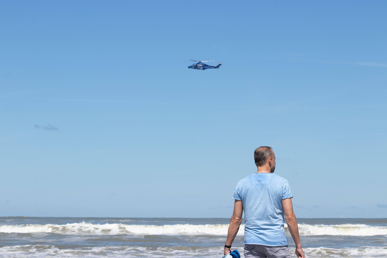 Een foto van een man op het strand van Ameland en een vliegtuig boven de zee