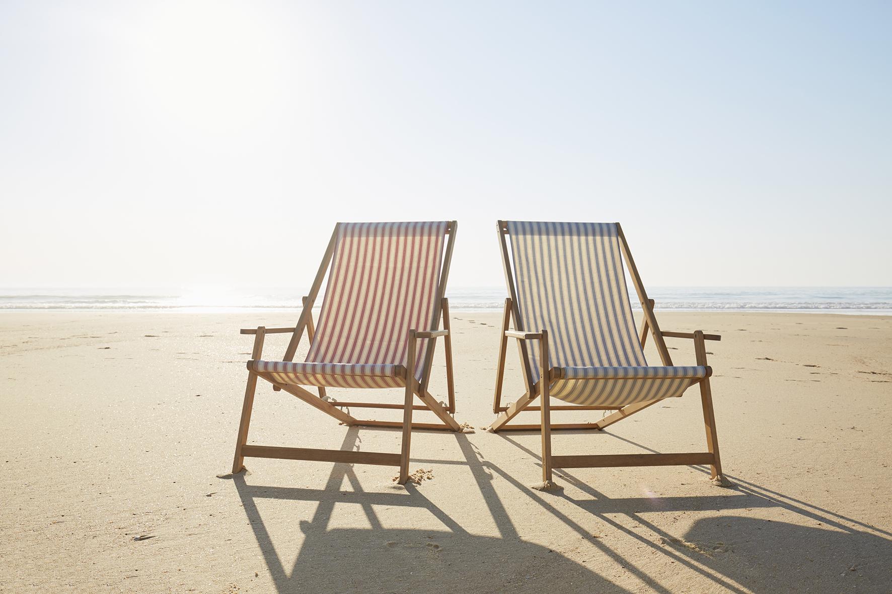 Op deze foto zie je twee strandstoelen op het strand staan