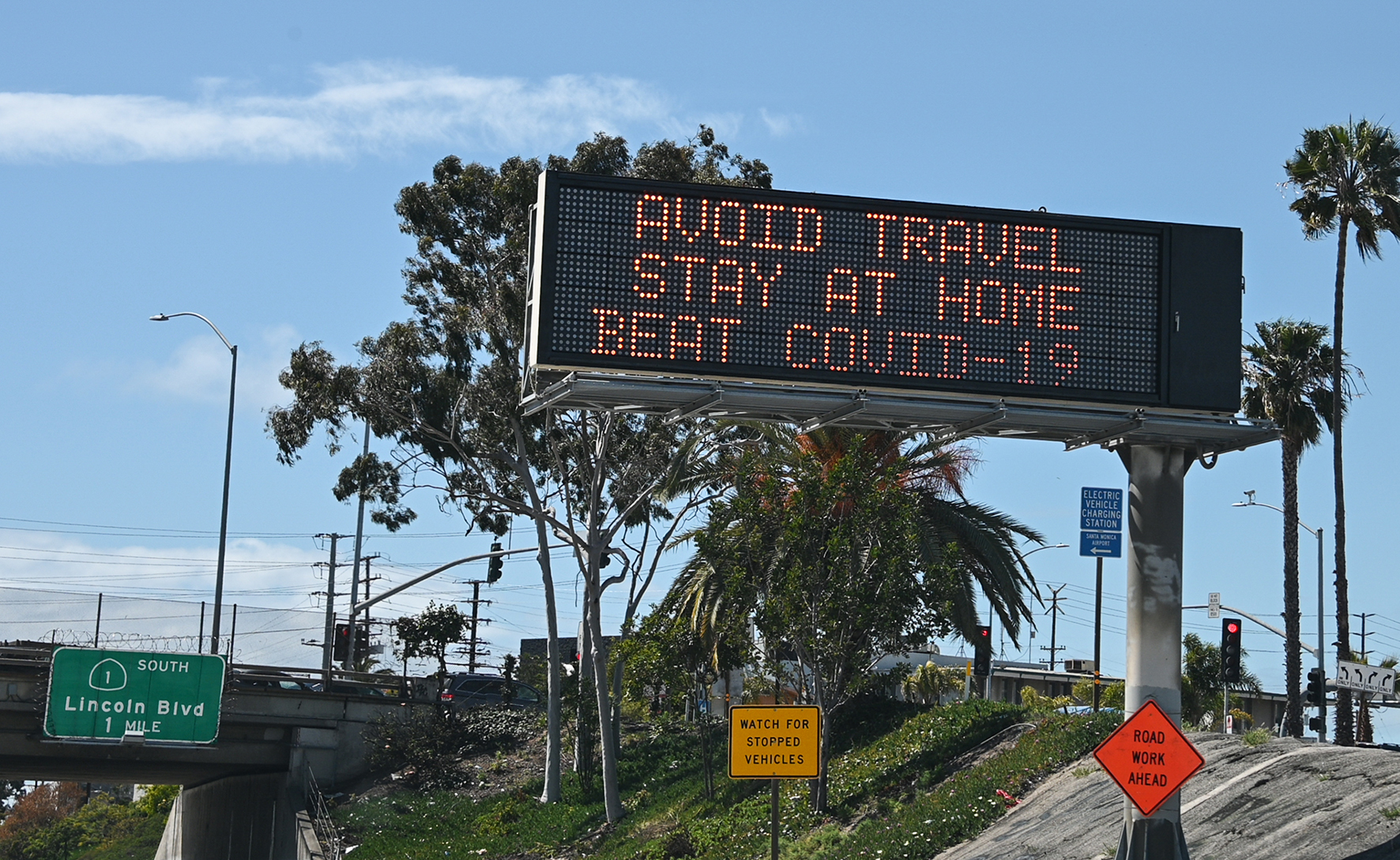 Op deze foto zie je een digitaal bord langs de highway in Los Angeles welke waarschuwd om thuis te blijven om COVID-19 zo min mogelijk te verspreiden