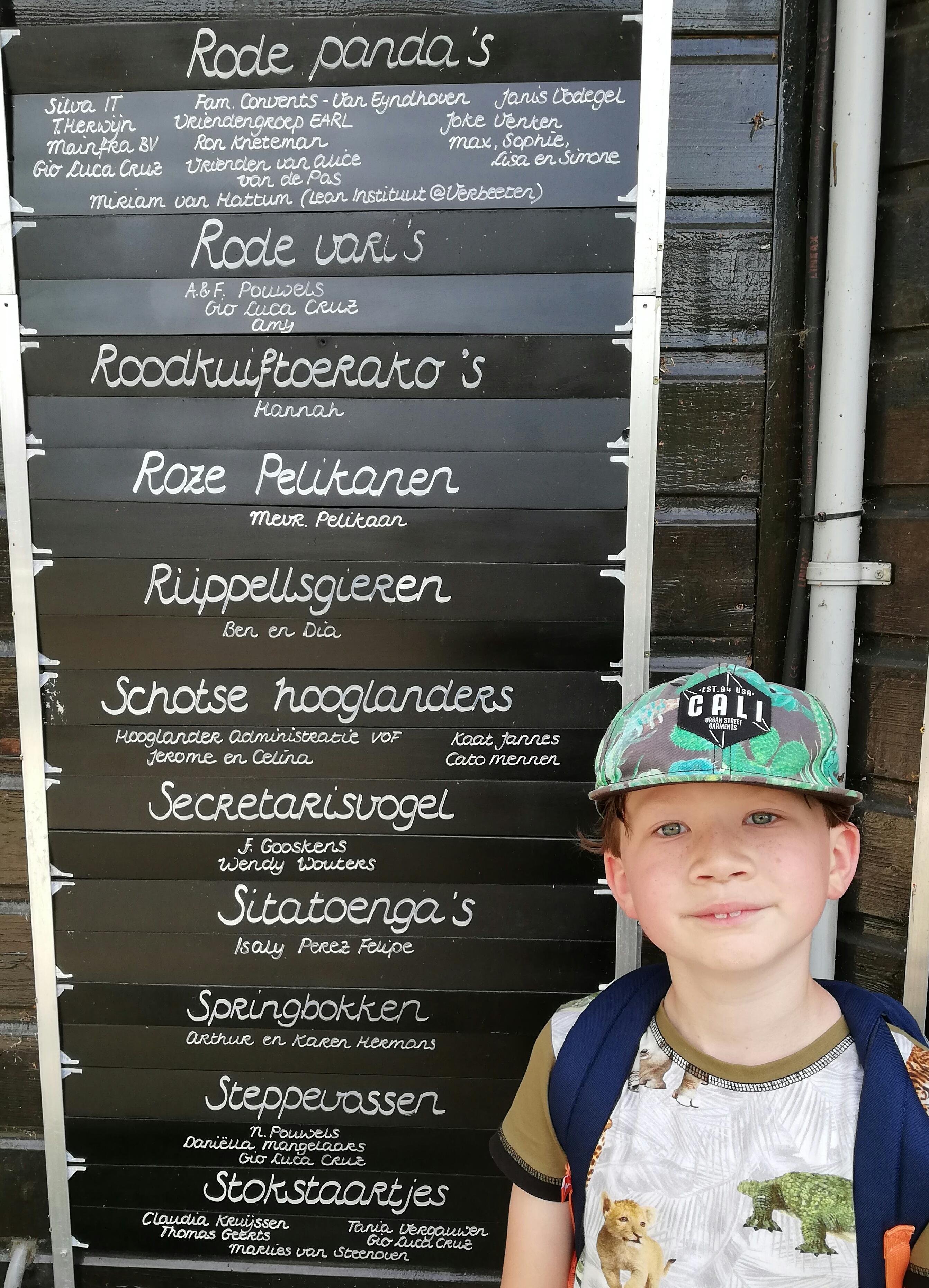 Een foto van Gio bij adoptiebordjes in Beekse Bergen