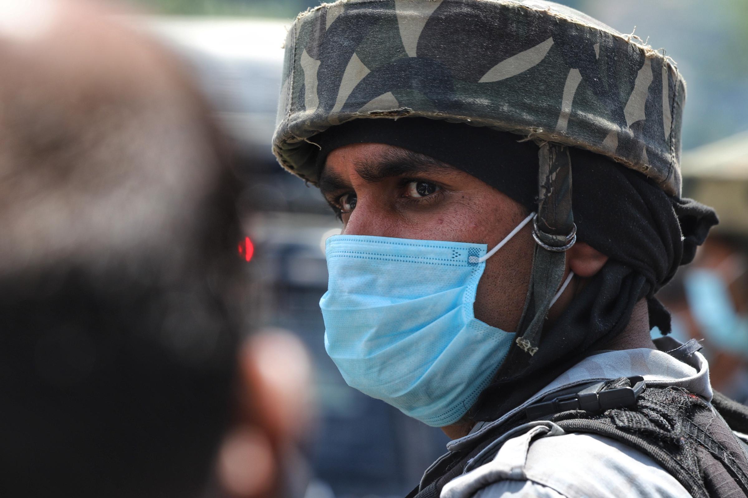 Een foto van een beveiliger met mondkapje in India
