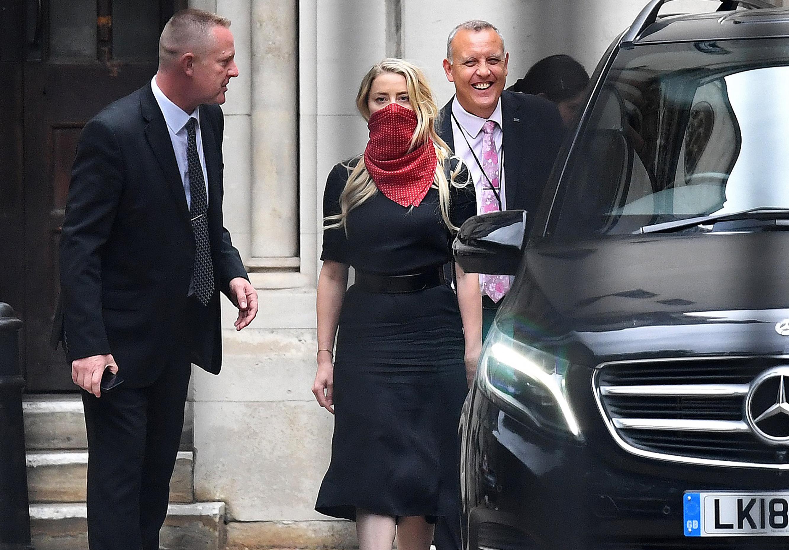 Een foto van de ook aanwezig Amber Heard, met mondkapje