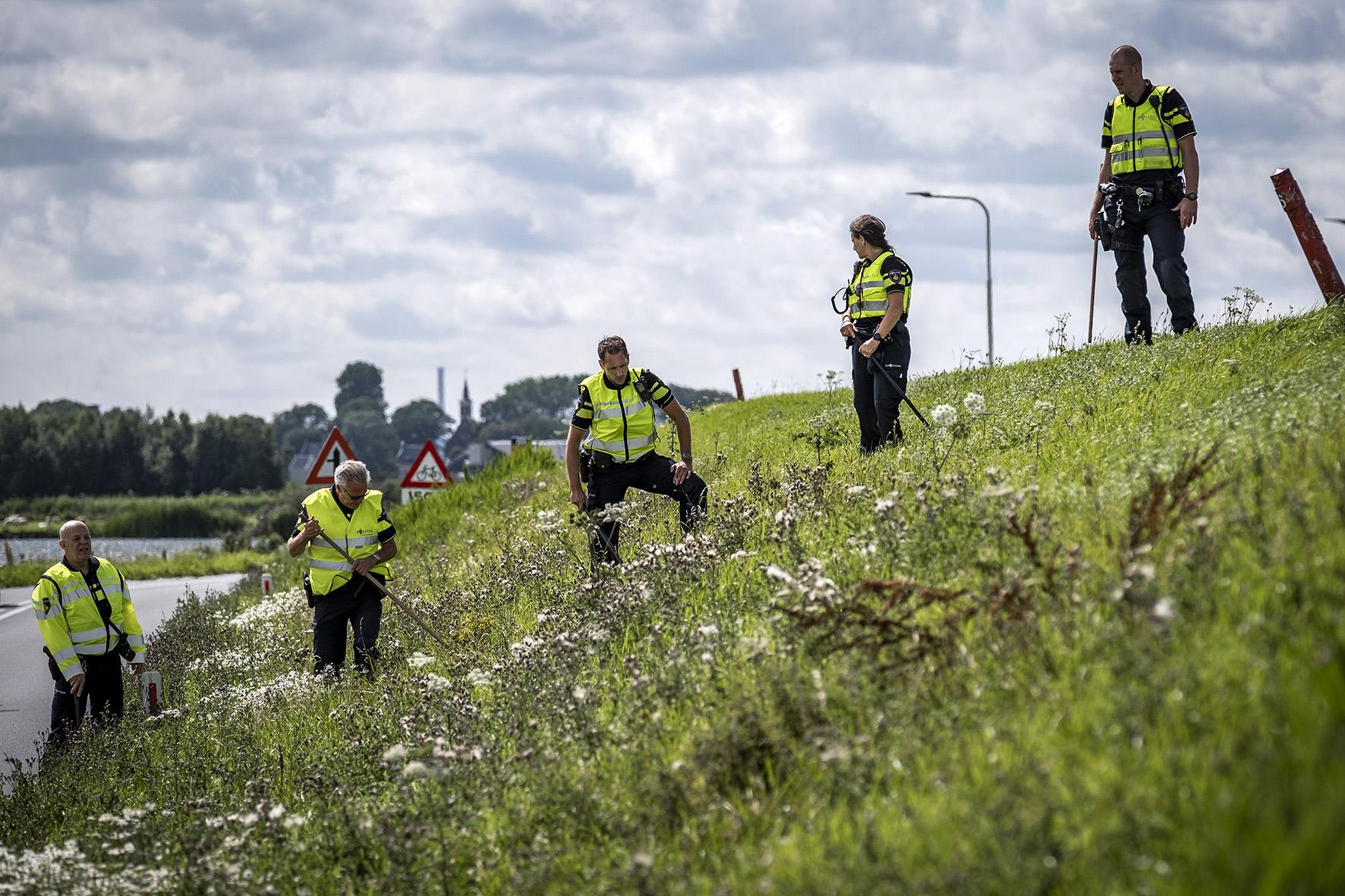 Op deze foto zie je politie doet die onderzoekdoekt in de berm op de plek waar een meisje van 14 jaar uit Marken is gevonden langs de dijk tussen Monnickendam en Marken. De politie is bezig met een zoektocht in de berm voor eventueel meer bewijs.
