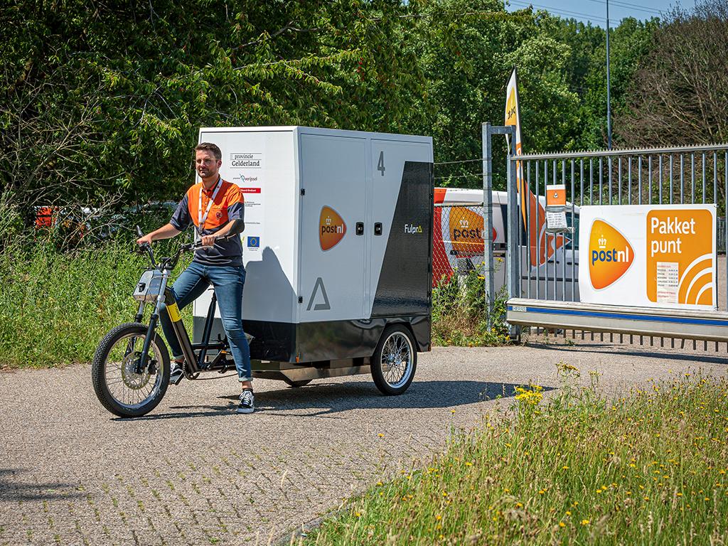 Een foto van een pakketjes-bezorger per fiets