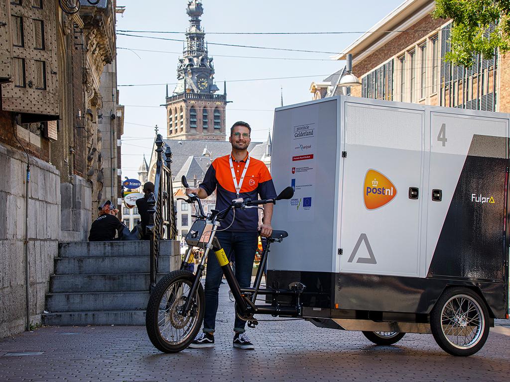 Een foto van een pakketjes-bezorger in een straat in Nijmegen