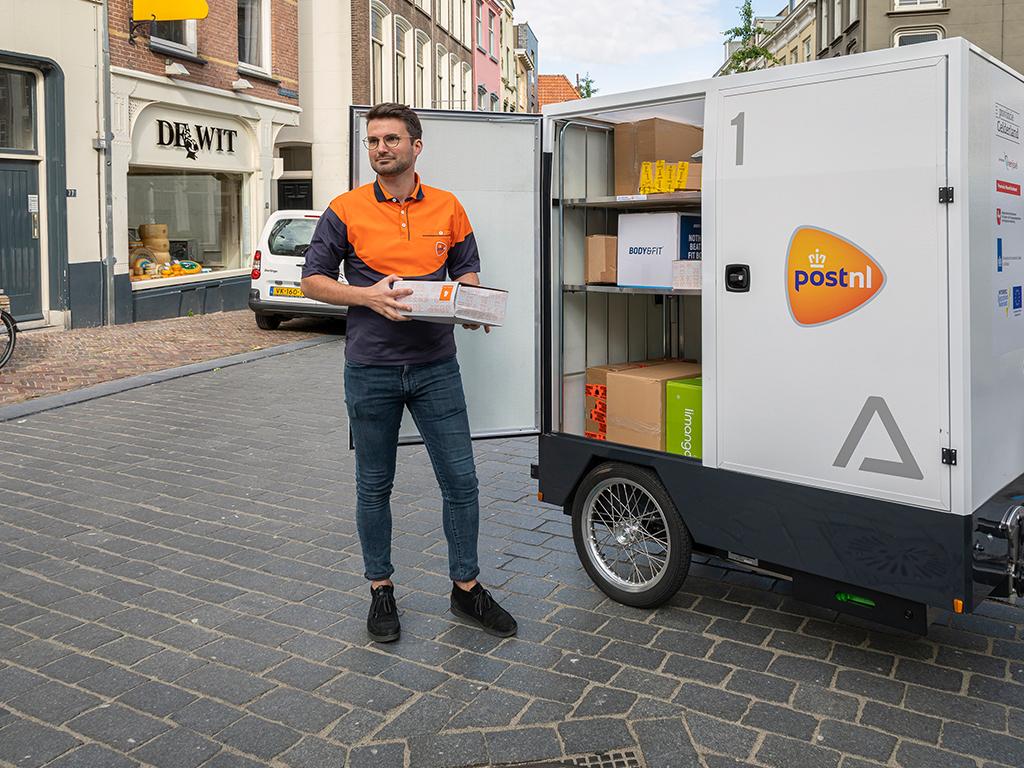 Een foto van een pakketbezorger bij de kast achter zijn fiets