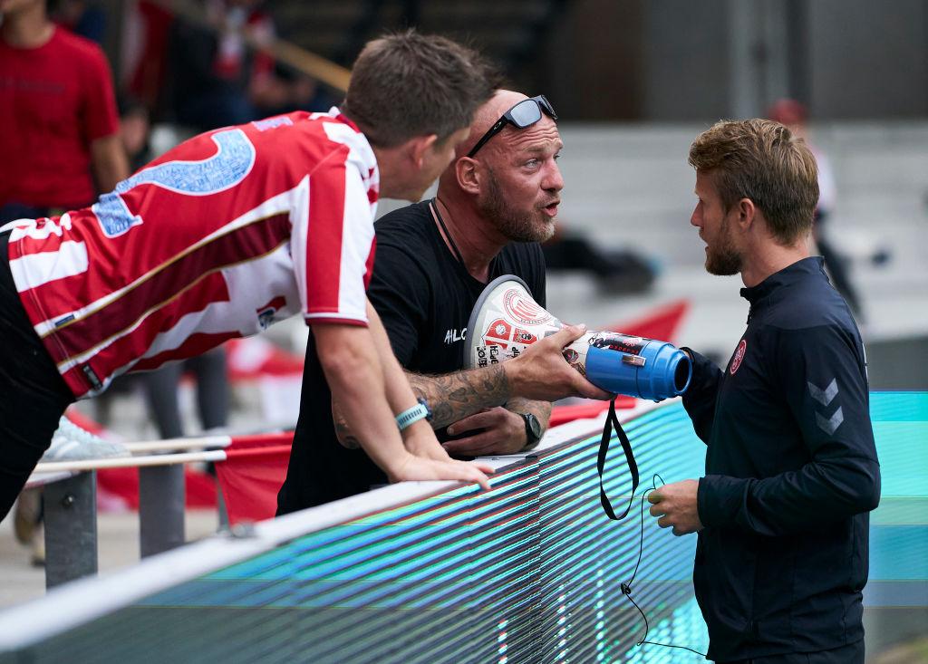 Een foto van een Deense assistent-trainer die het publiek verzoekt om uit elkaar te gaan zitten.
