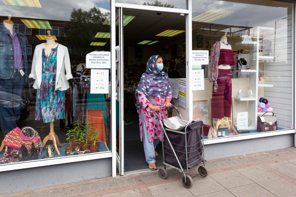 Een foto van een vrouw met een mondkapje bij een Engelse winkel