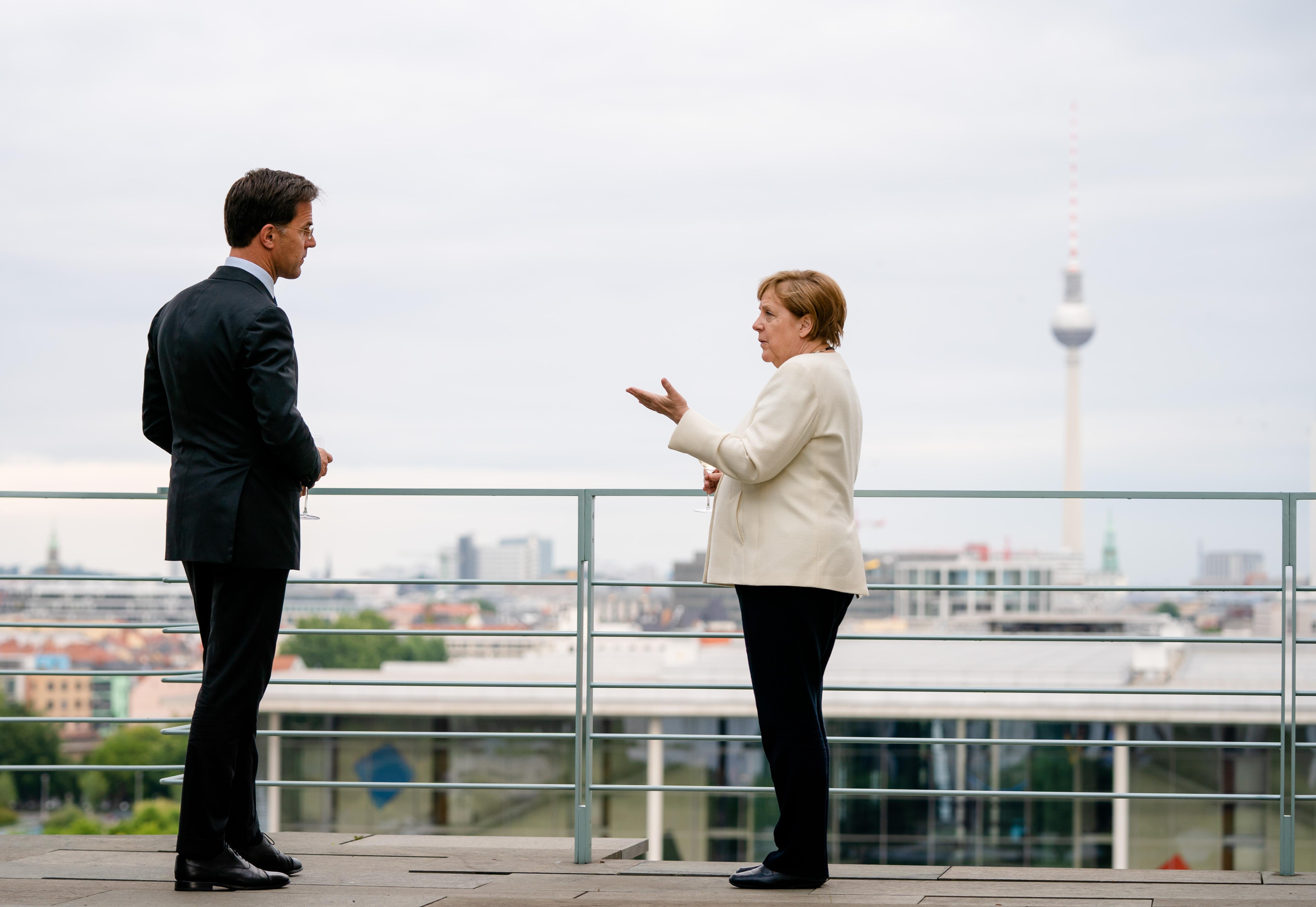 Een foto van Mark Rutte op coronabezoek bij Angela Merkel