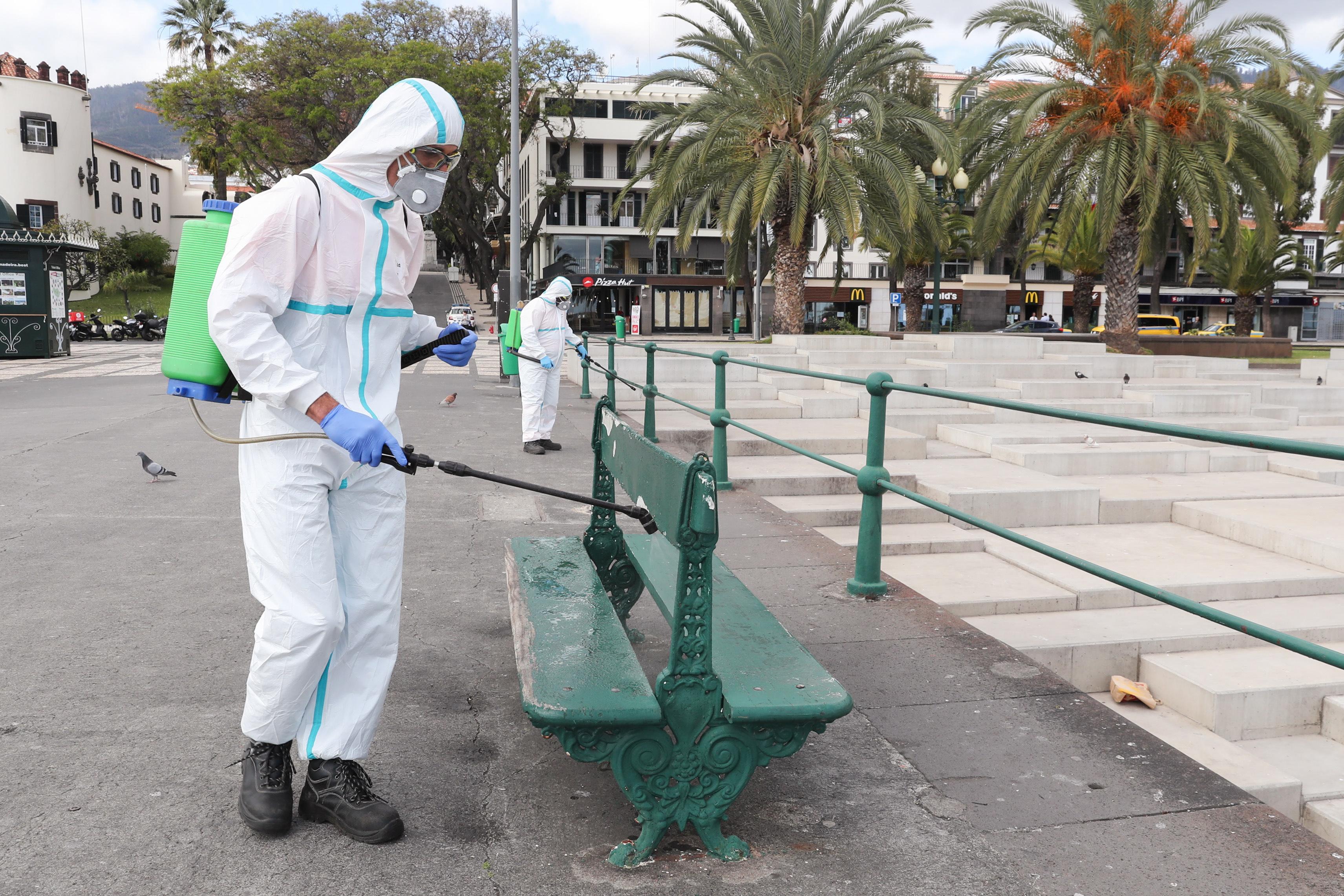 Een foto van een man die een bankje op het eiland Madeira ontsmet