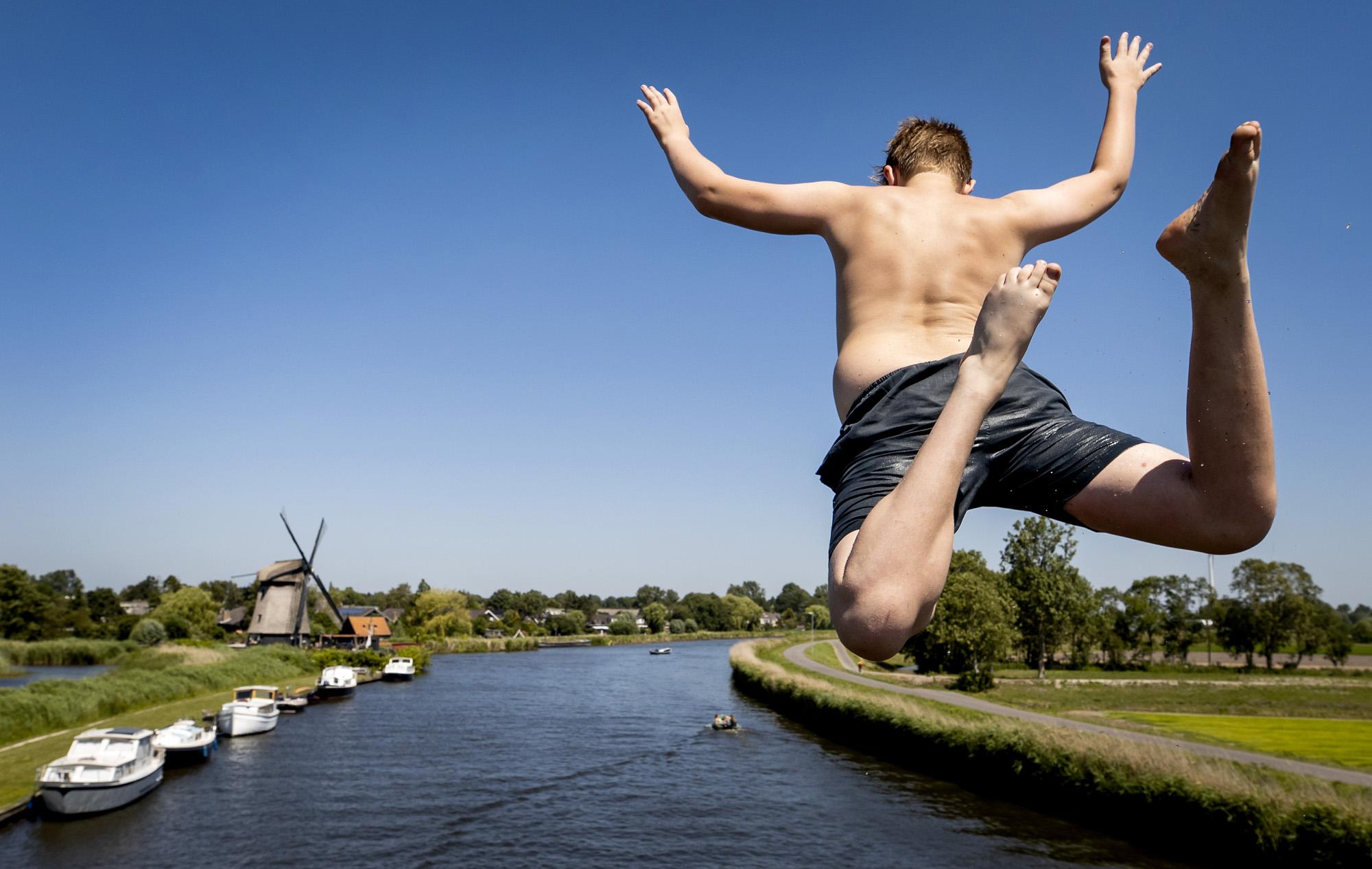 Een foto van een jongetje dat vanaf een brug in het water springt