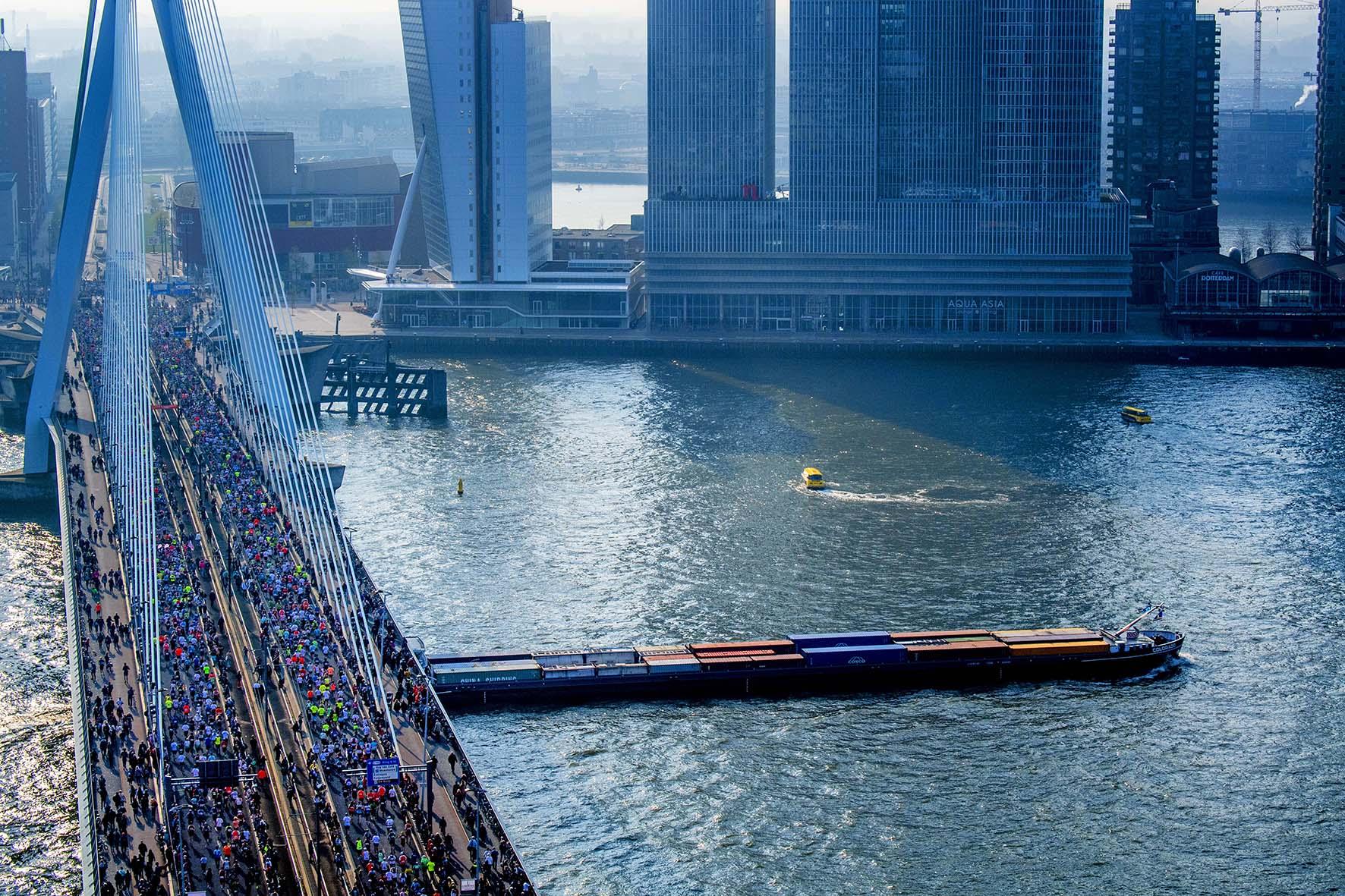 Op deze foto zie je lopers gaan over de Erasmusbrug tijdens de NN marathon van Rotterdam.