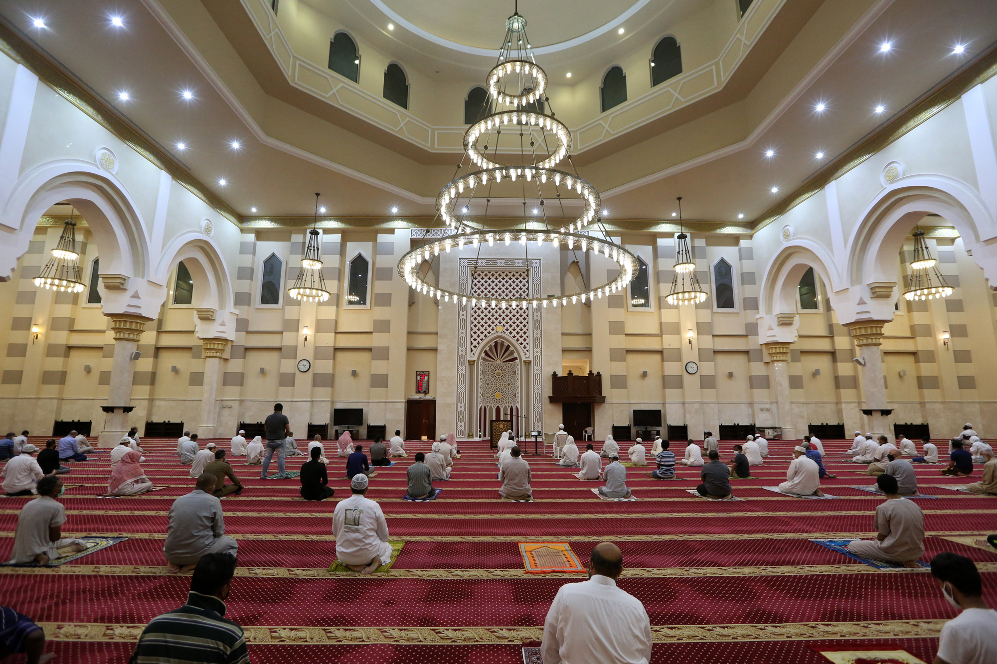 Een foto van een moskee in Mekka waarin mensen veilig afstand van elkaar houden