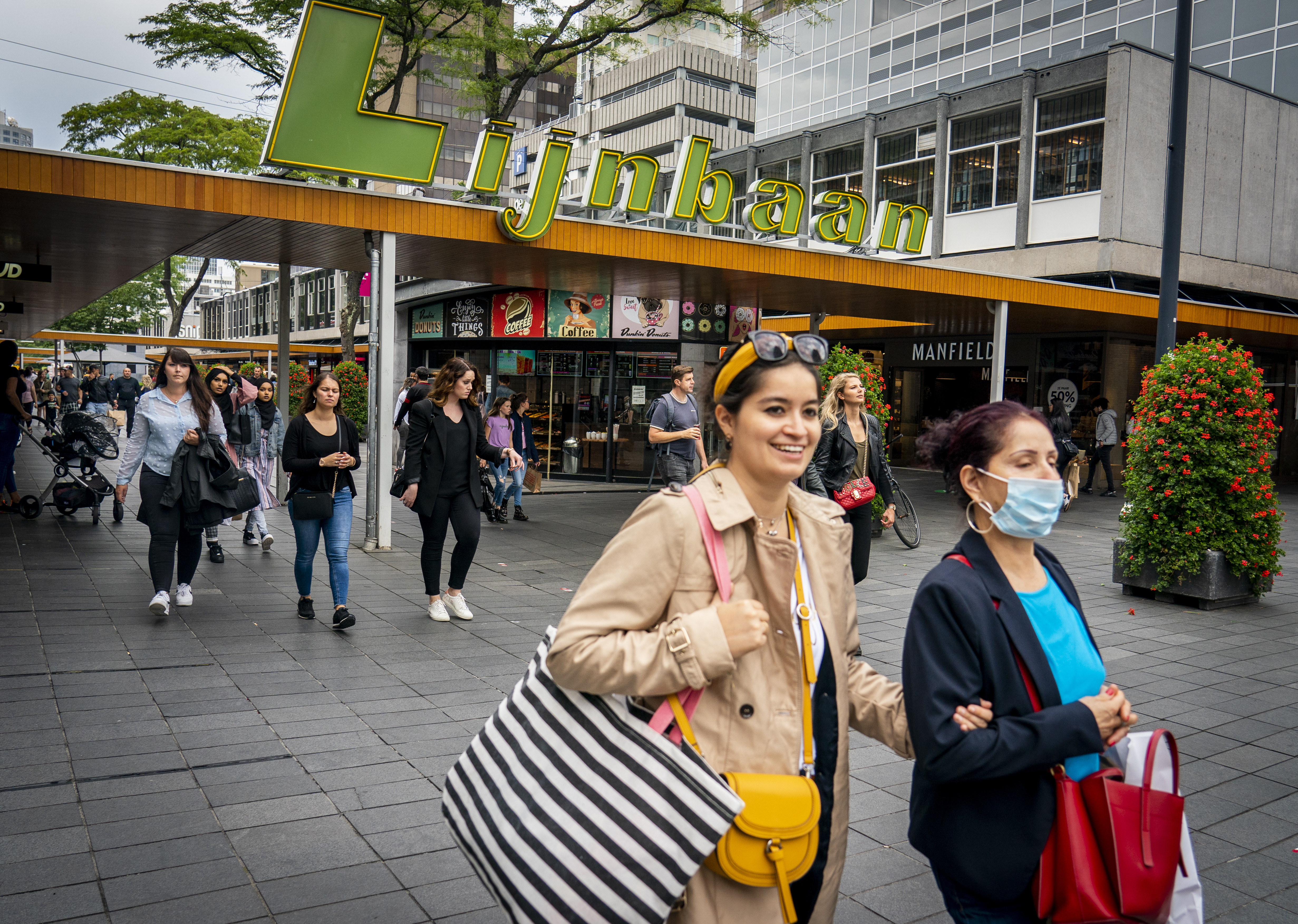 Een foto van twee meisjes in Rotterdam, één zonder mondkapje, één met