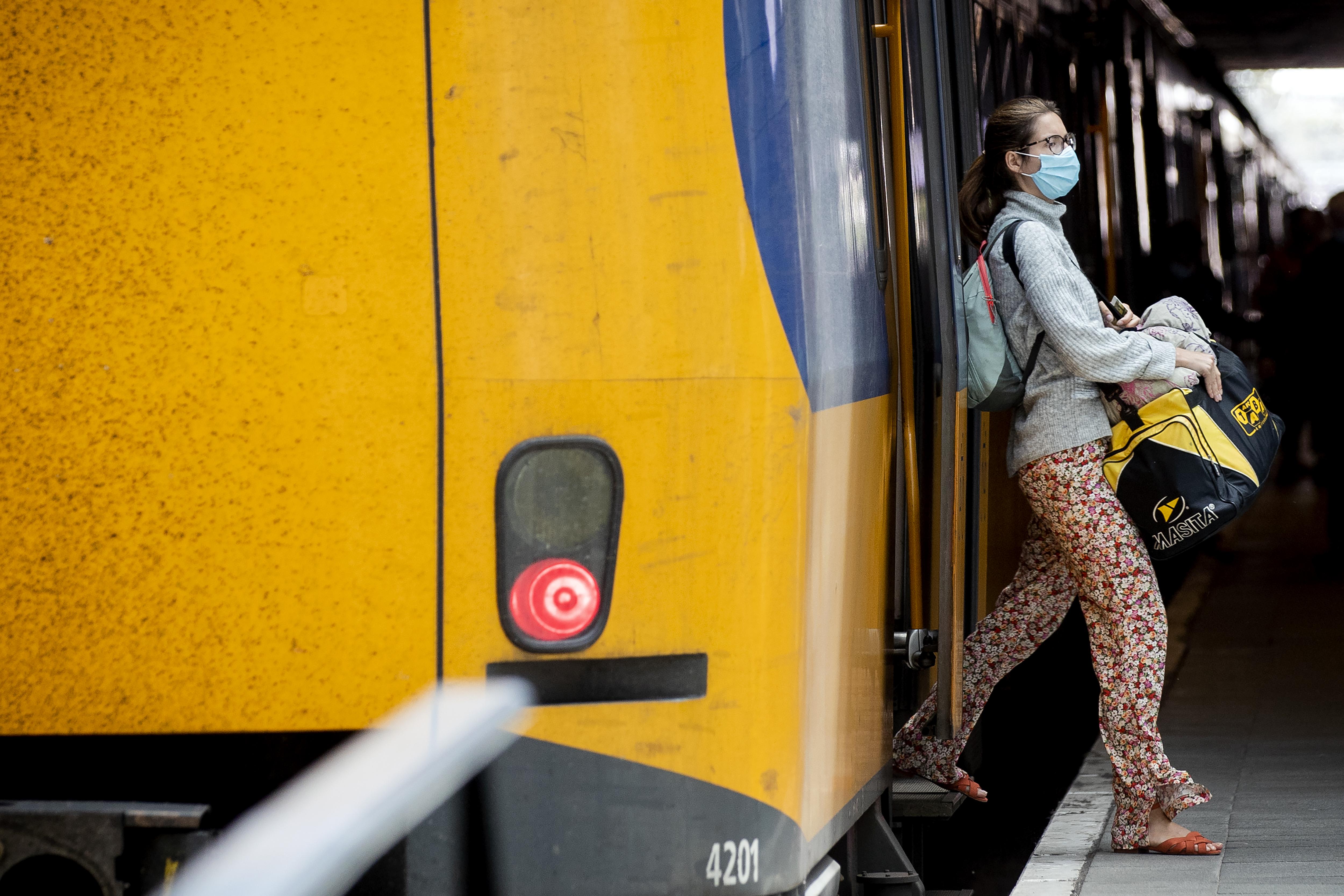 Een foto van een meisje met een mondkapje dat uit de trein stapt