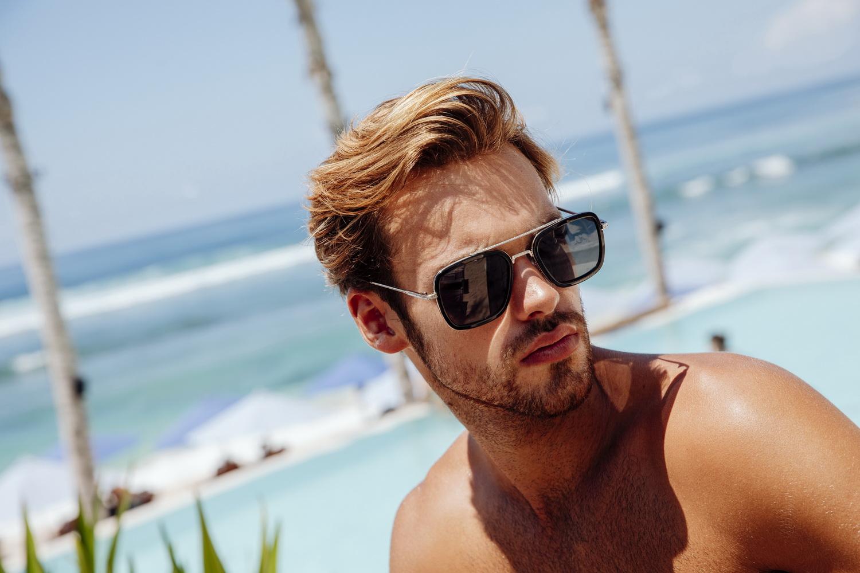 Een foto van een man met een zonnebril op het strand